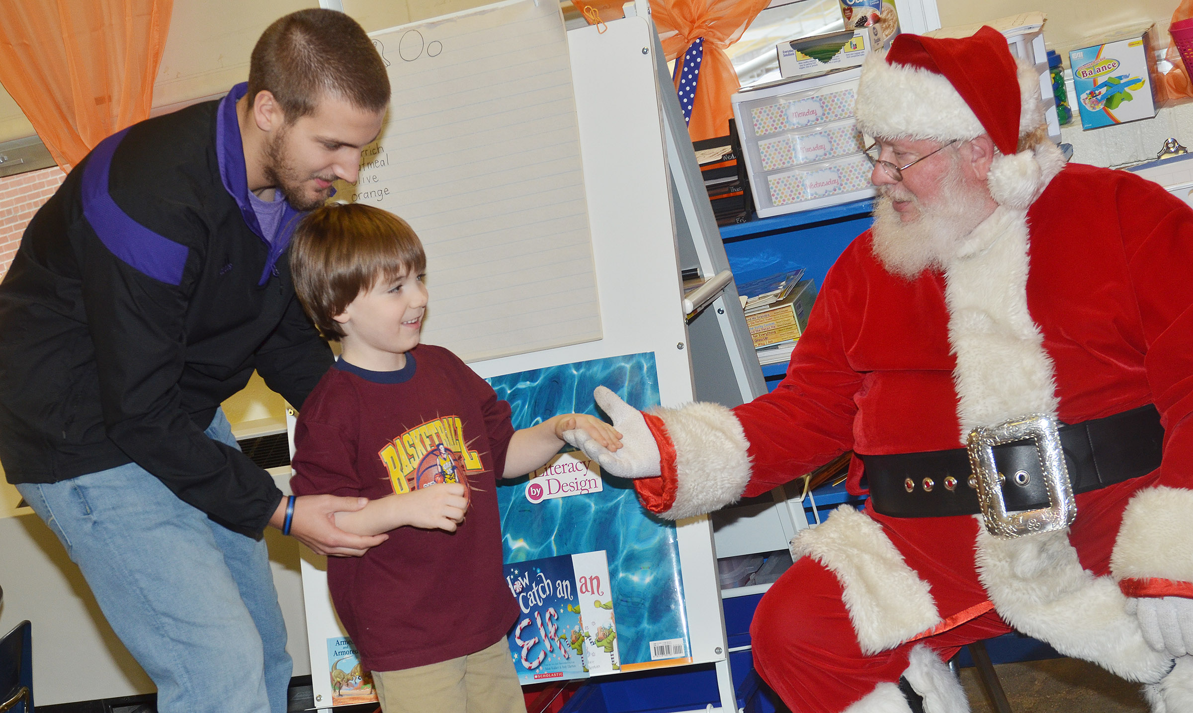 CES kindergartener Finley Williams greets Santa, with some help from assistant Zach Durham.