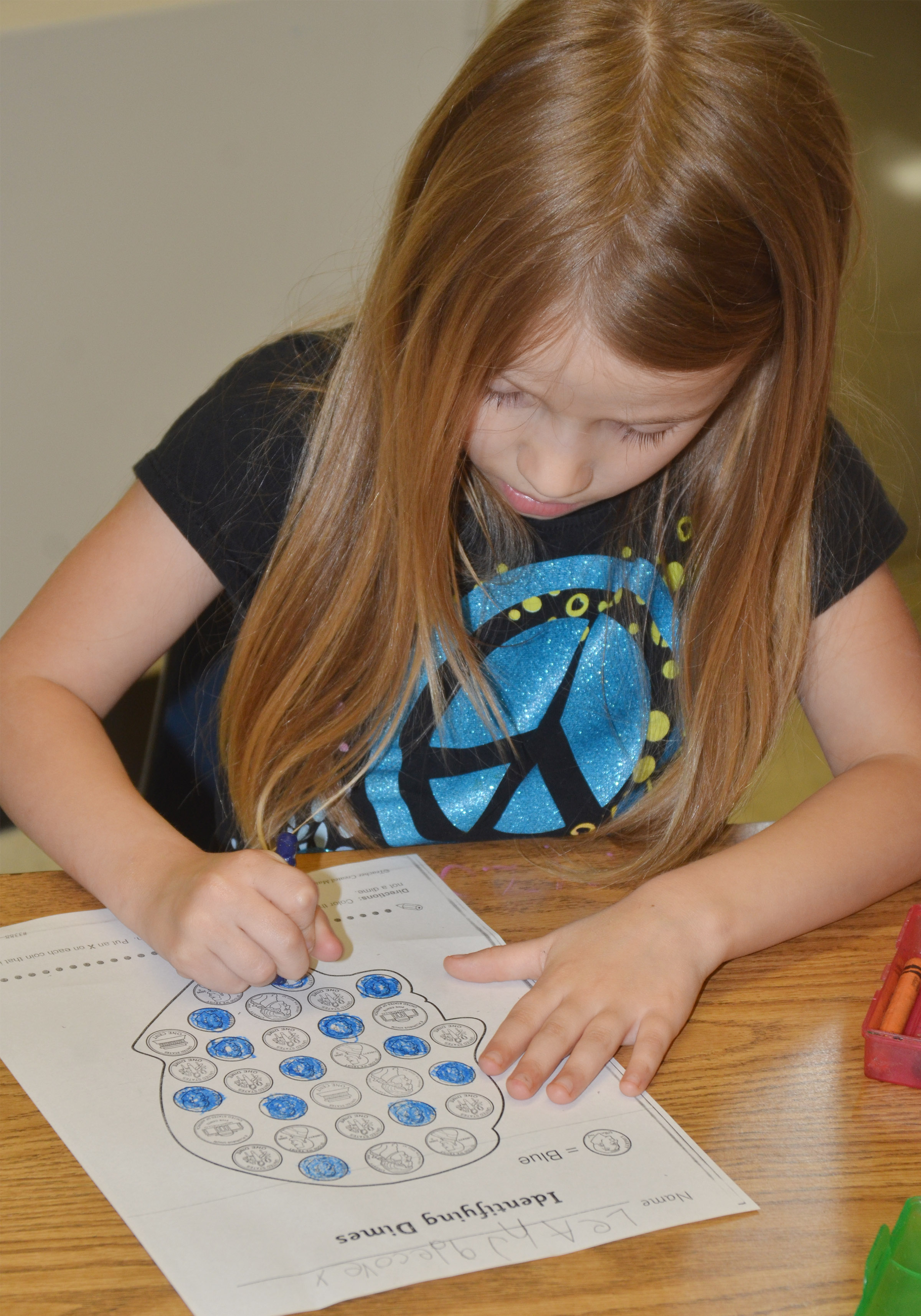 CES kindergartener Leah Covey colors dimes.