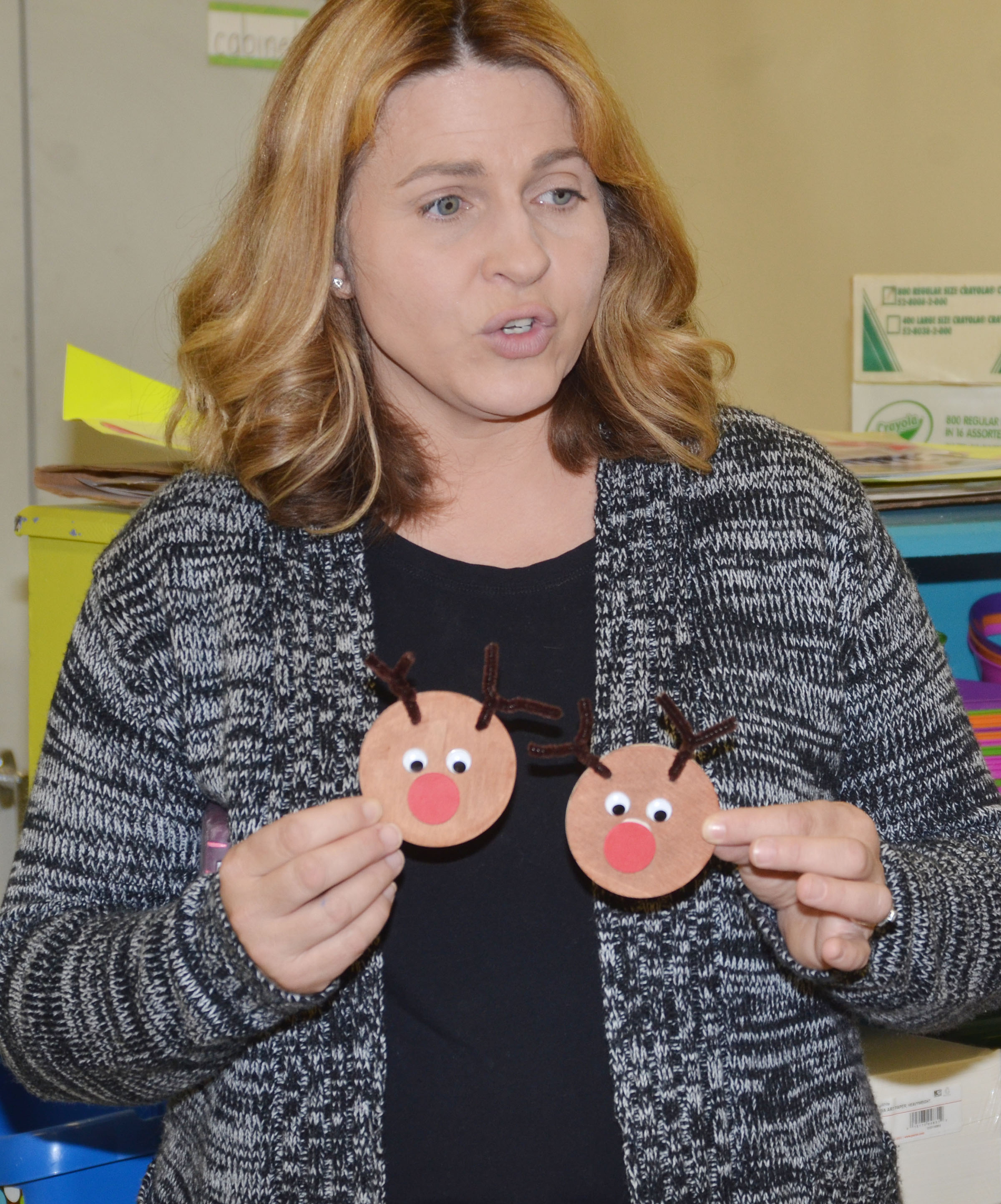 "CES Guidance Counselor Sonya Orberson shows students the ornaments they will make for ""Project Rudolph."""