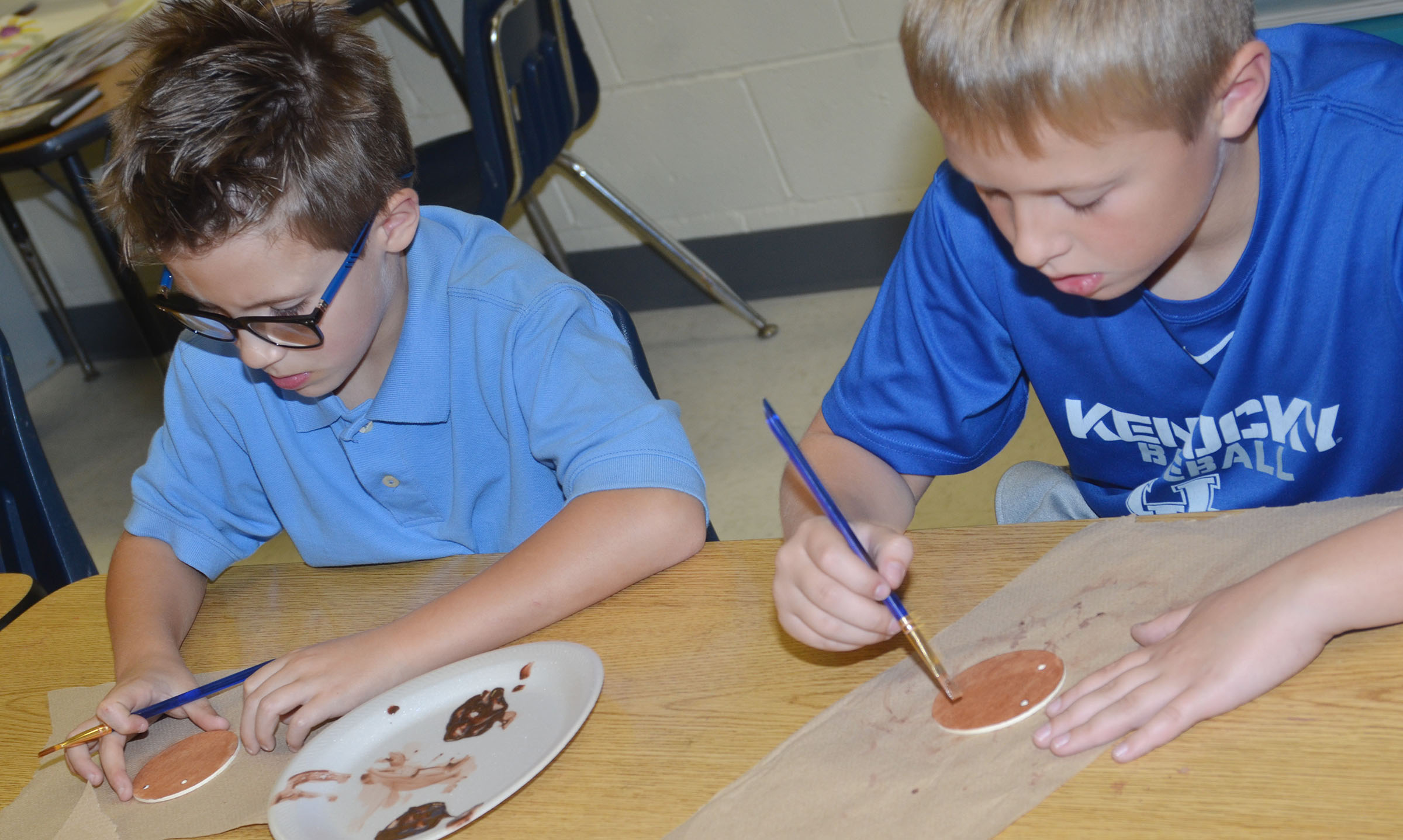 CES second-graders Dalton Shively, at left, and Evan Lockridge paint their ornaments.