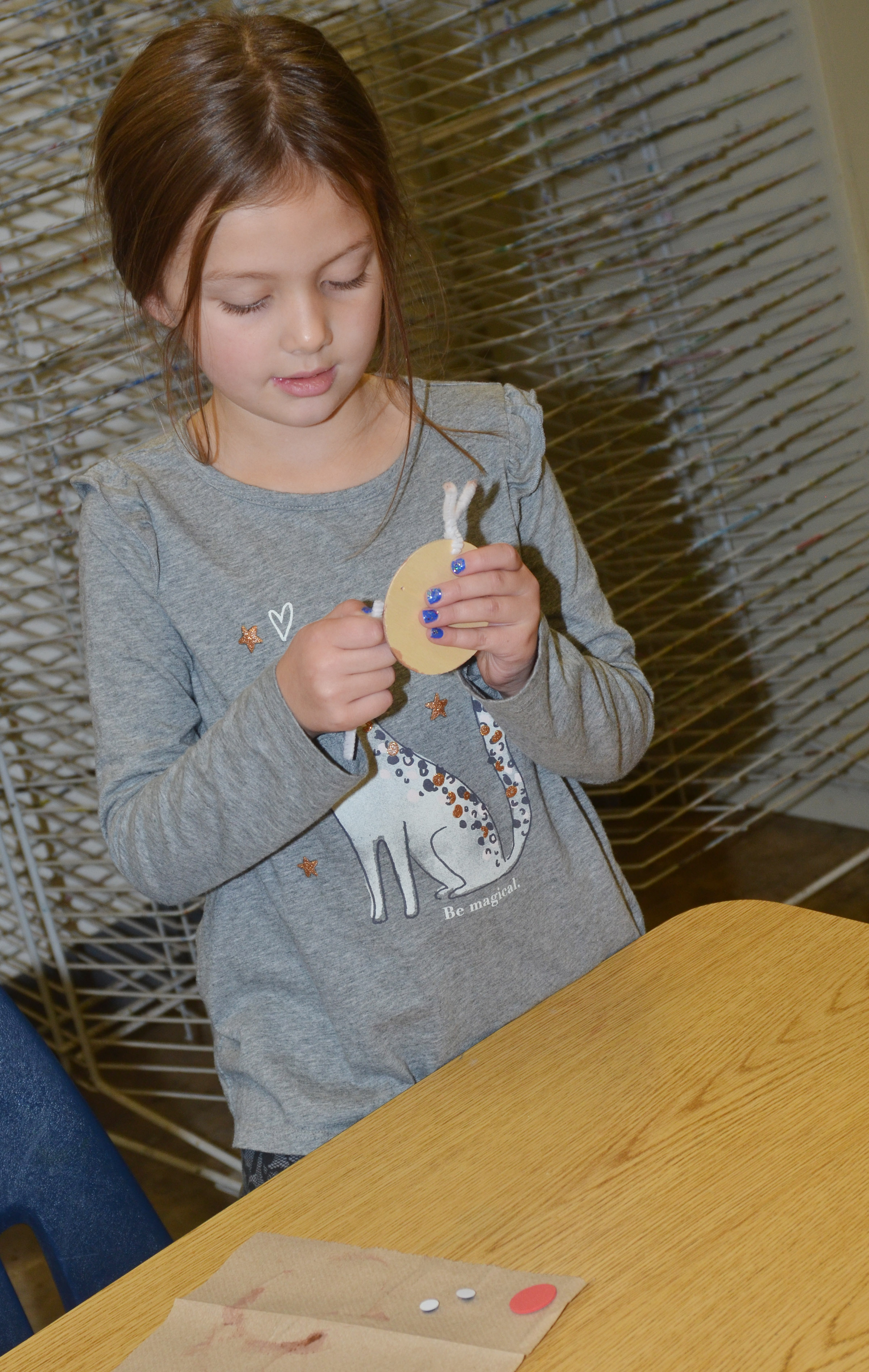 CES first-grader Delaney Staton adds antlers to her reindeer ornaments.