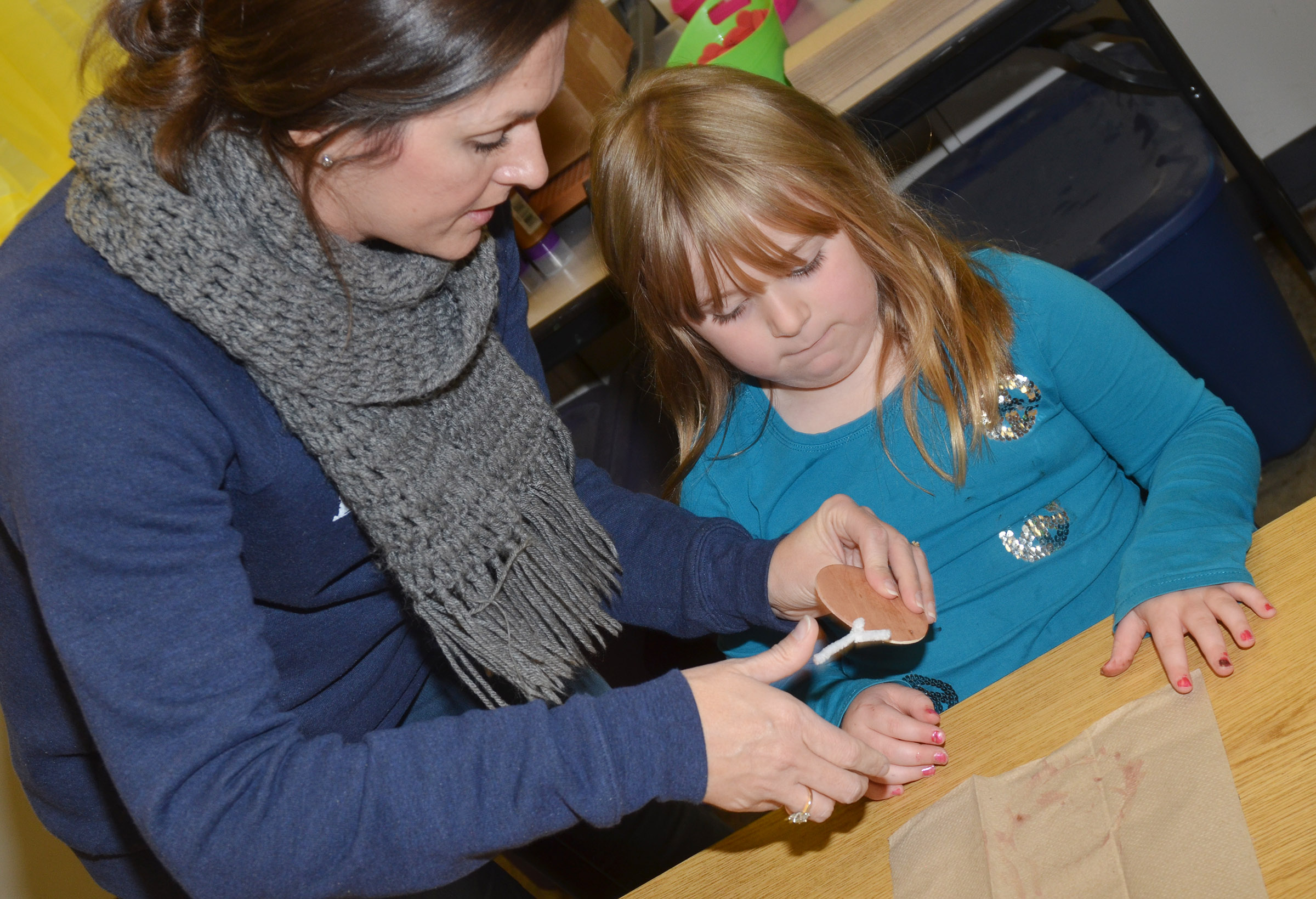 CES art teacher Adrienne Hash helps first-grader Briley Sapp add antlers to her reindeer ornaments.