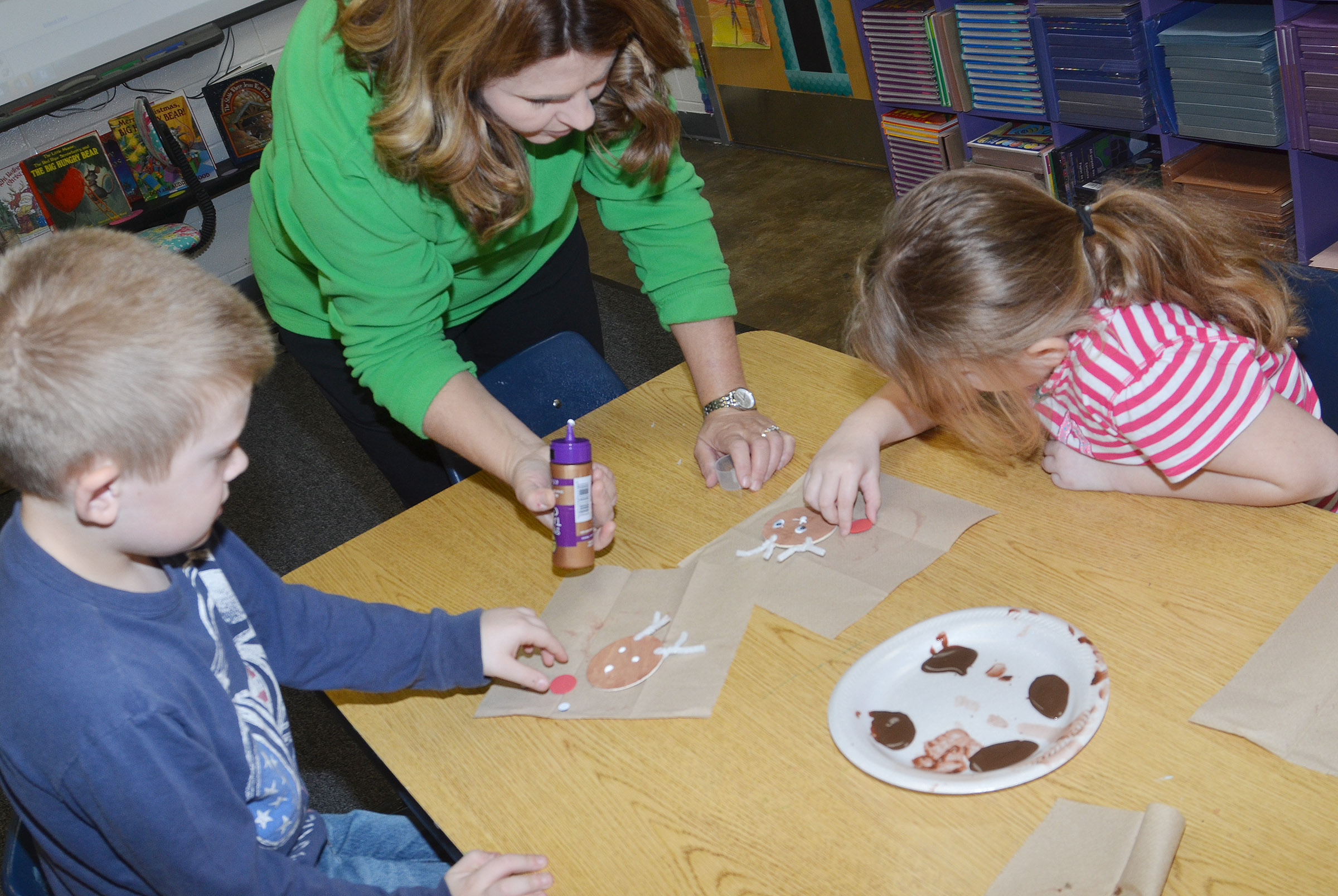 CES Guidance Counselor Sonya Orberson helps first-graders Gage Henderson, at left, and Laurna McKenzie add eyes and a nose to their reindeer ornaments.