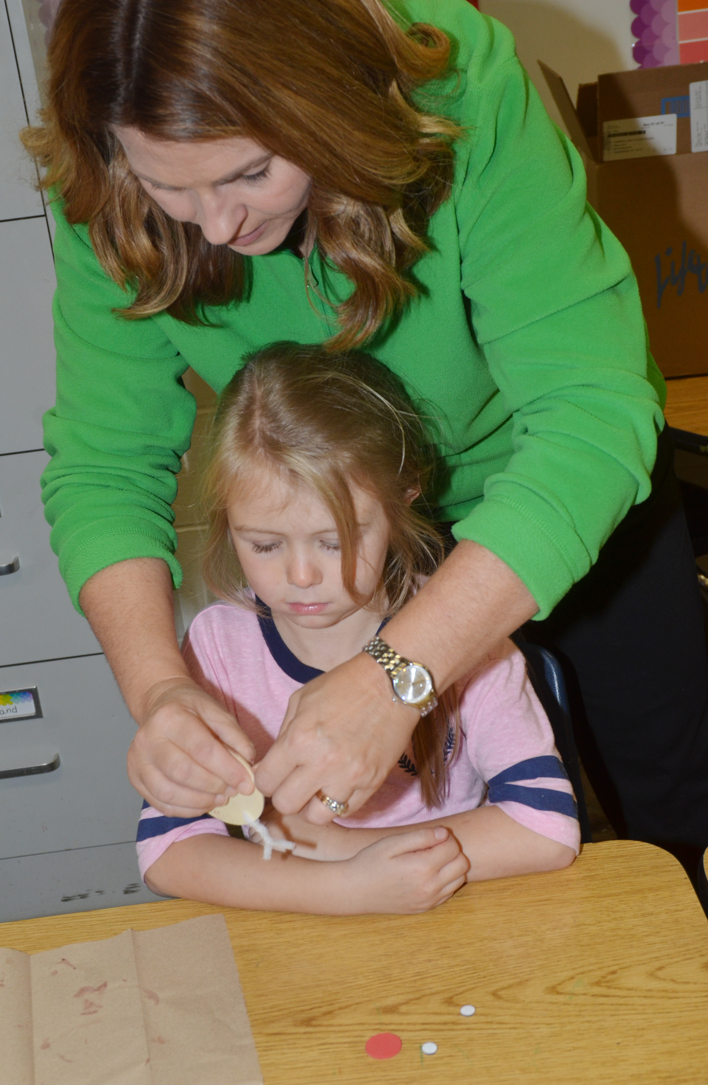 CES Guidance Counselor Sonya Orberson helps first-grader Jewell Brewster add antlers to her reindeer ornament.