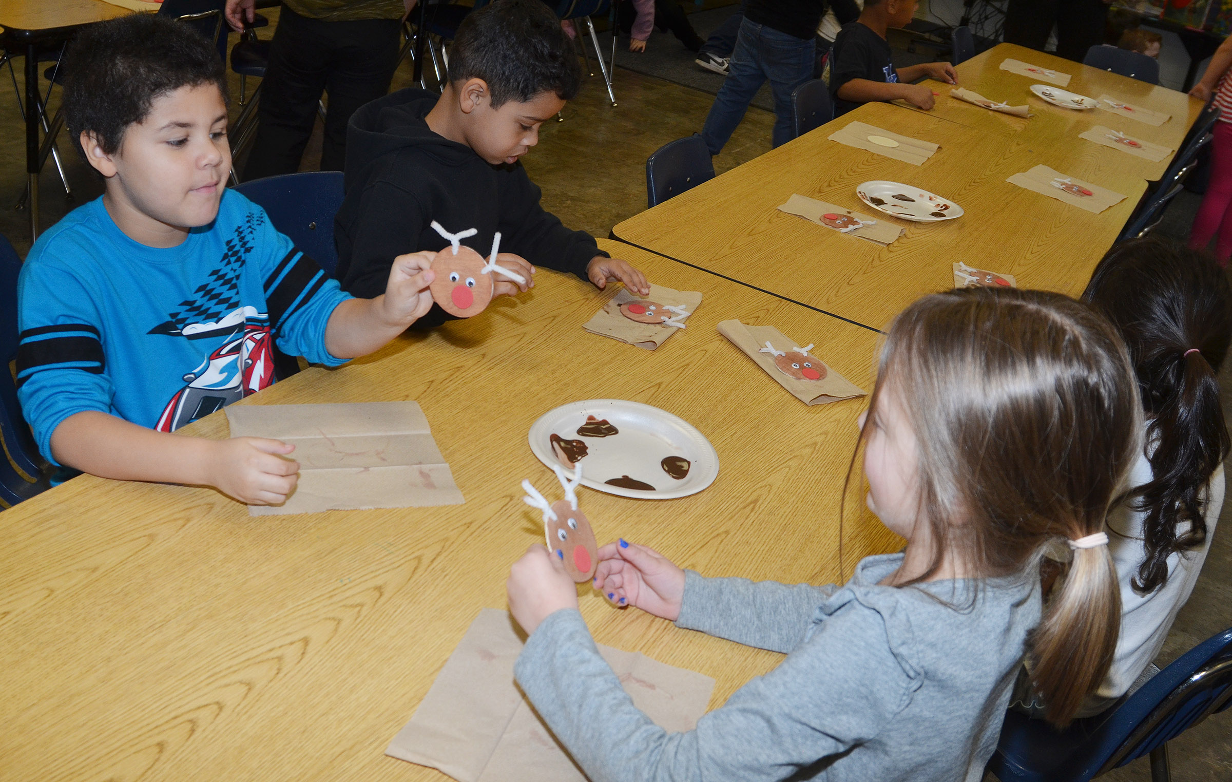 CES first-graders NyJah Vaught, at left, and Delaney Staton show each other their finished reindeer ornaments.