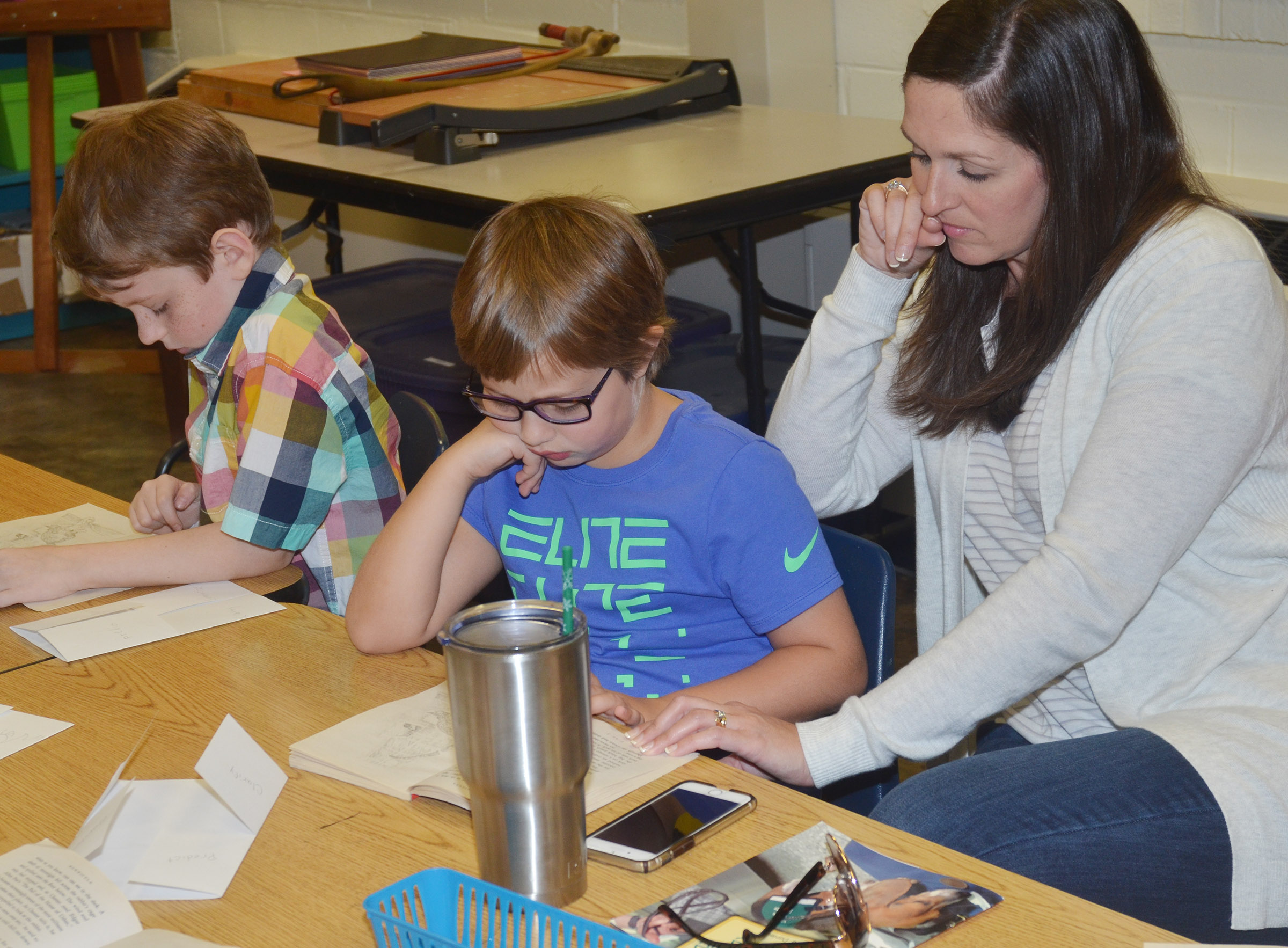 CES art teacher Adrienne Hash listens as her reading students read. Pictured are Jayden Cox and Addelyn Dooley.