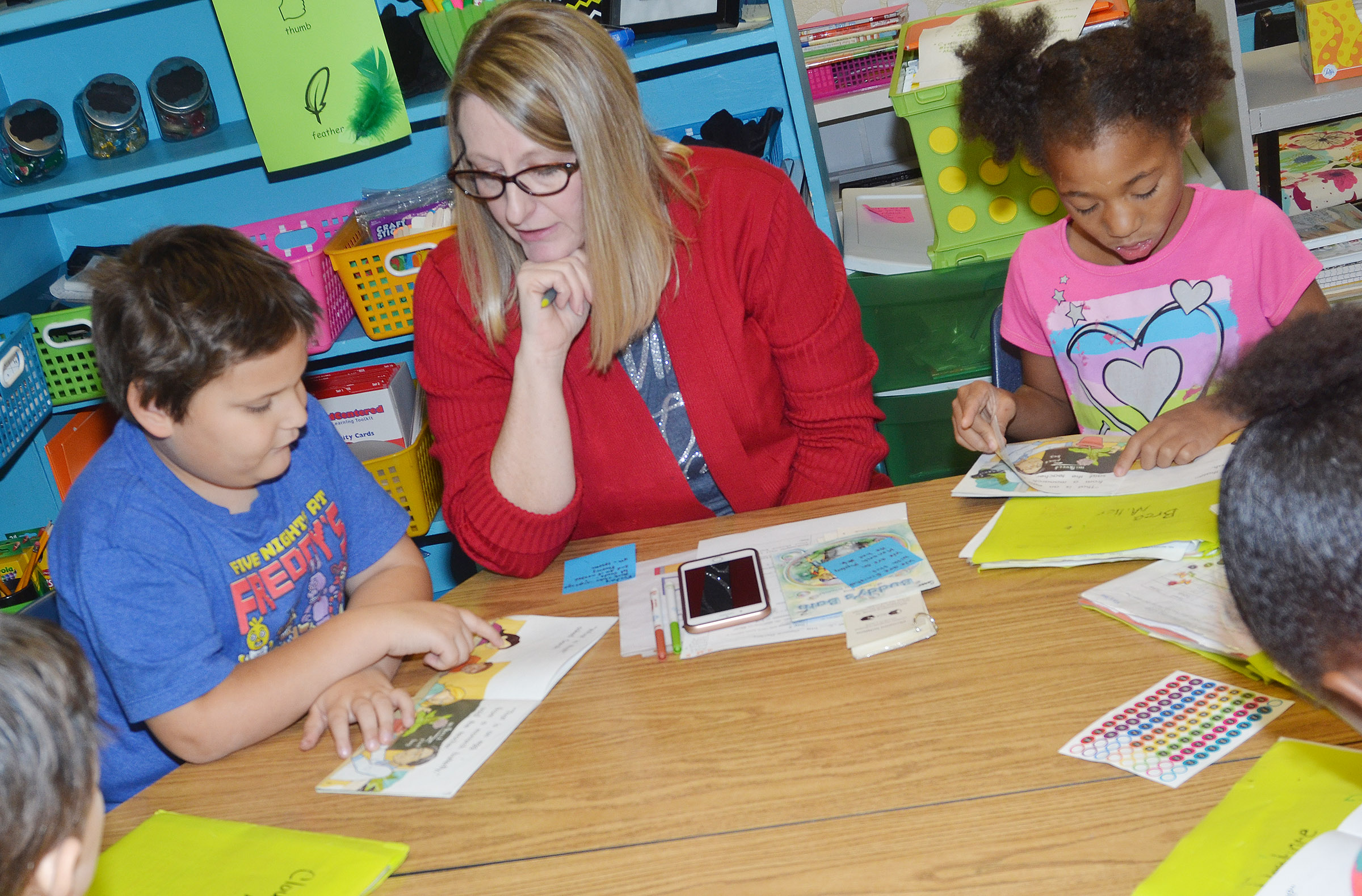 CES reading interventionist Laura Dicken reads with first-graders Cloud Malone, at left, and Brea Miller.