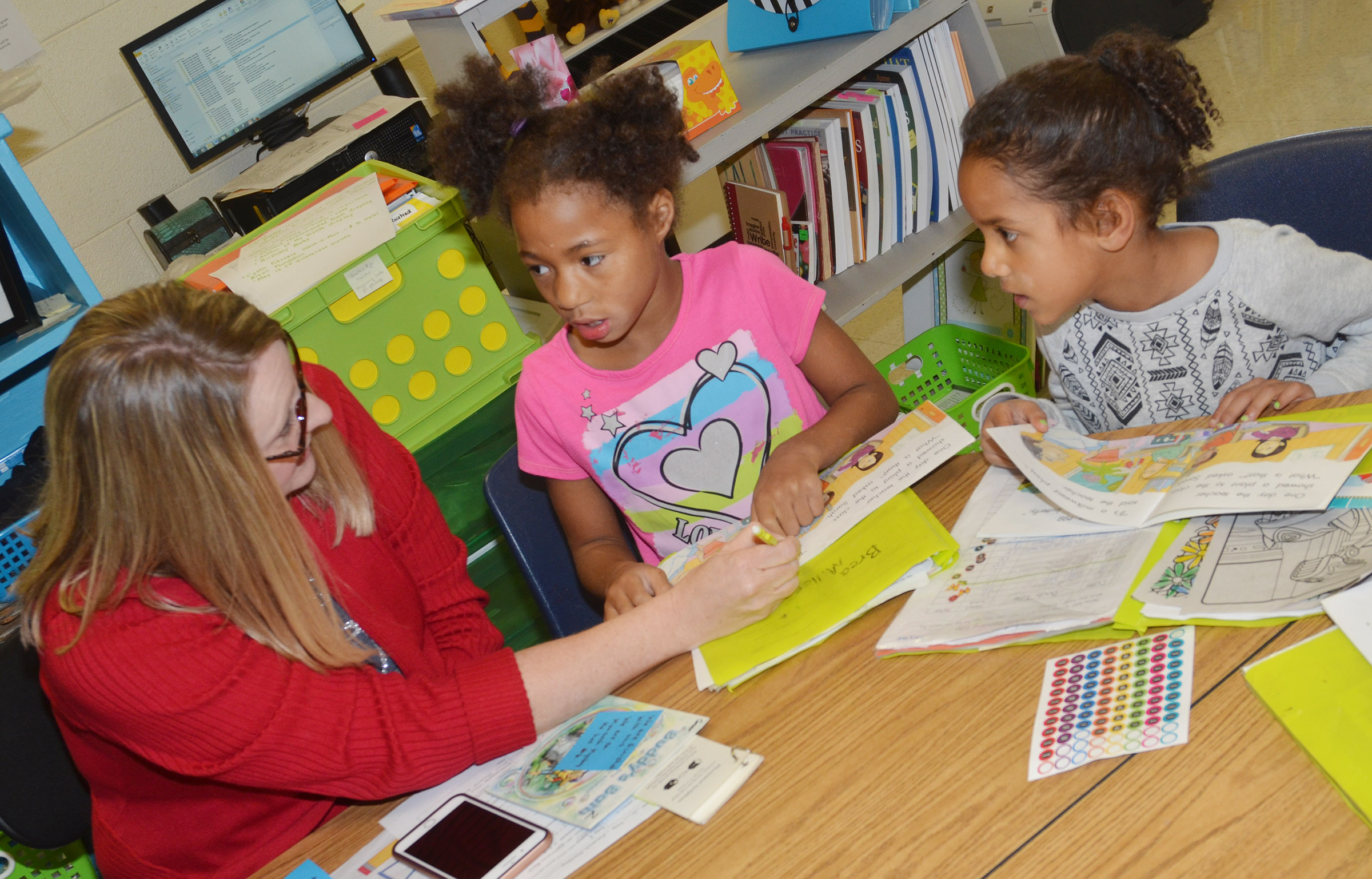 CES reading interventionist Laura Dicken reads with first-graders Brea Miller, center, and Kaylee Thompson.