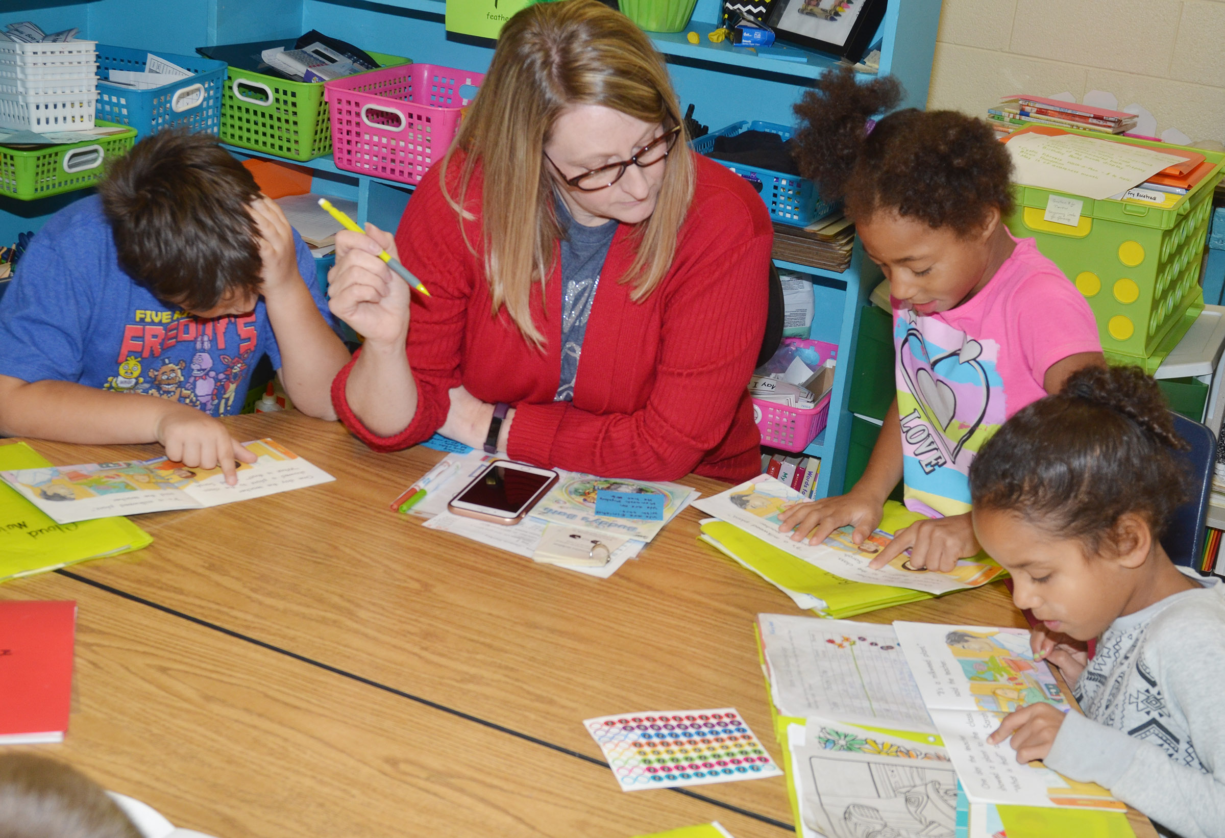 CES reading interventionist Laura Dicken reads with, from left, first-graders Cloud Malone, Brea Miller and Kaylee Thompson.