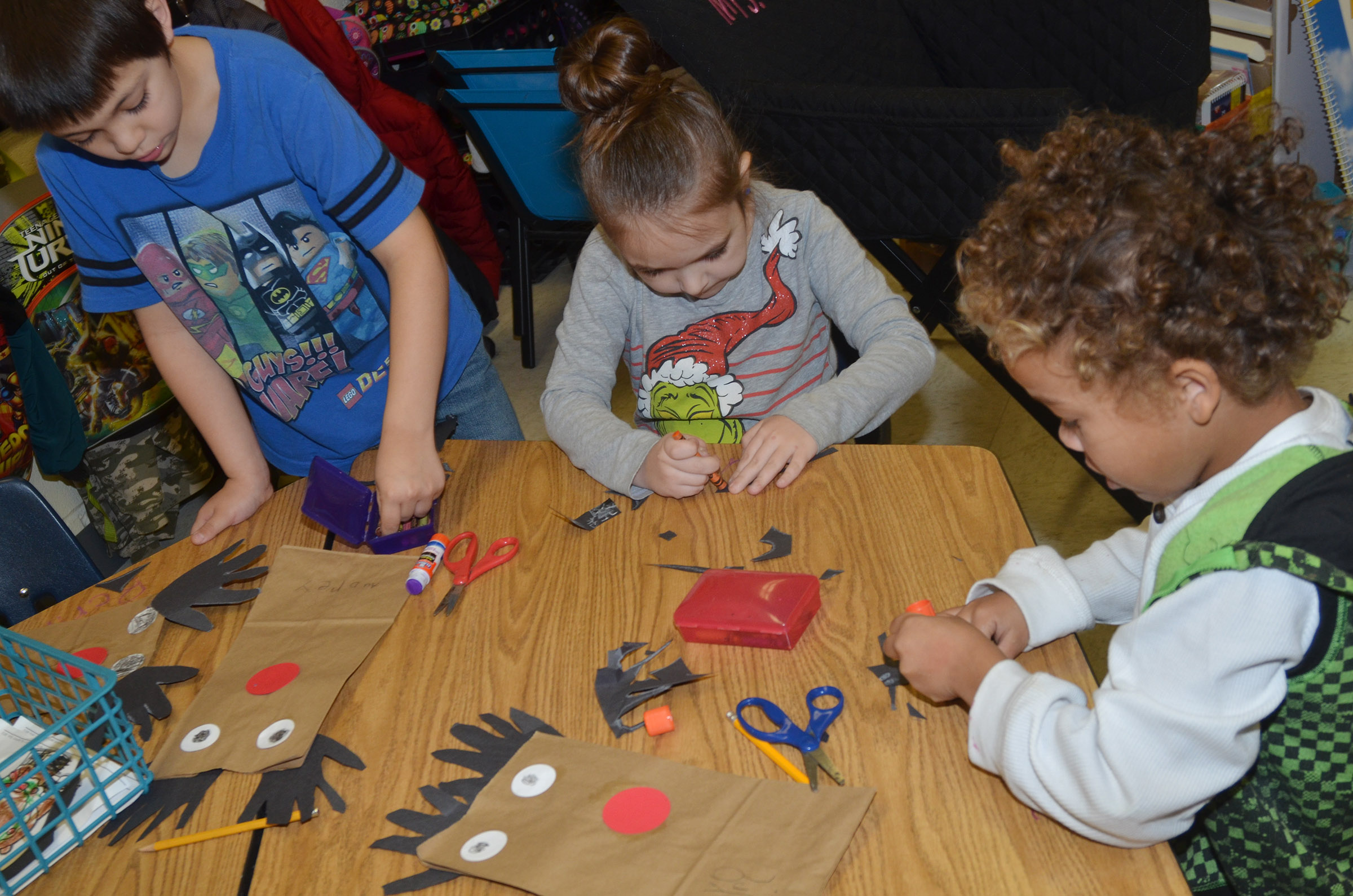 From left, CES kindergarteners Keagan Shearer, Aubrey Allen and Dyra Welch cut out their antlers.