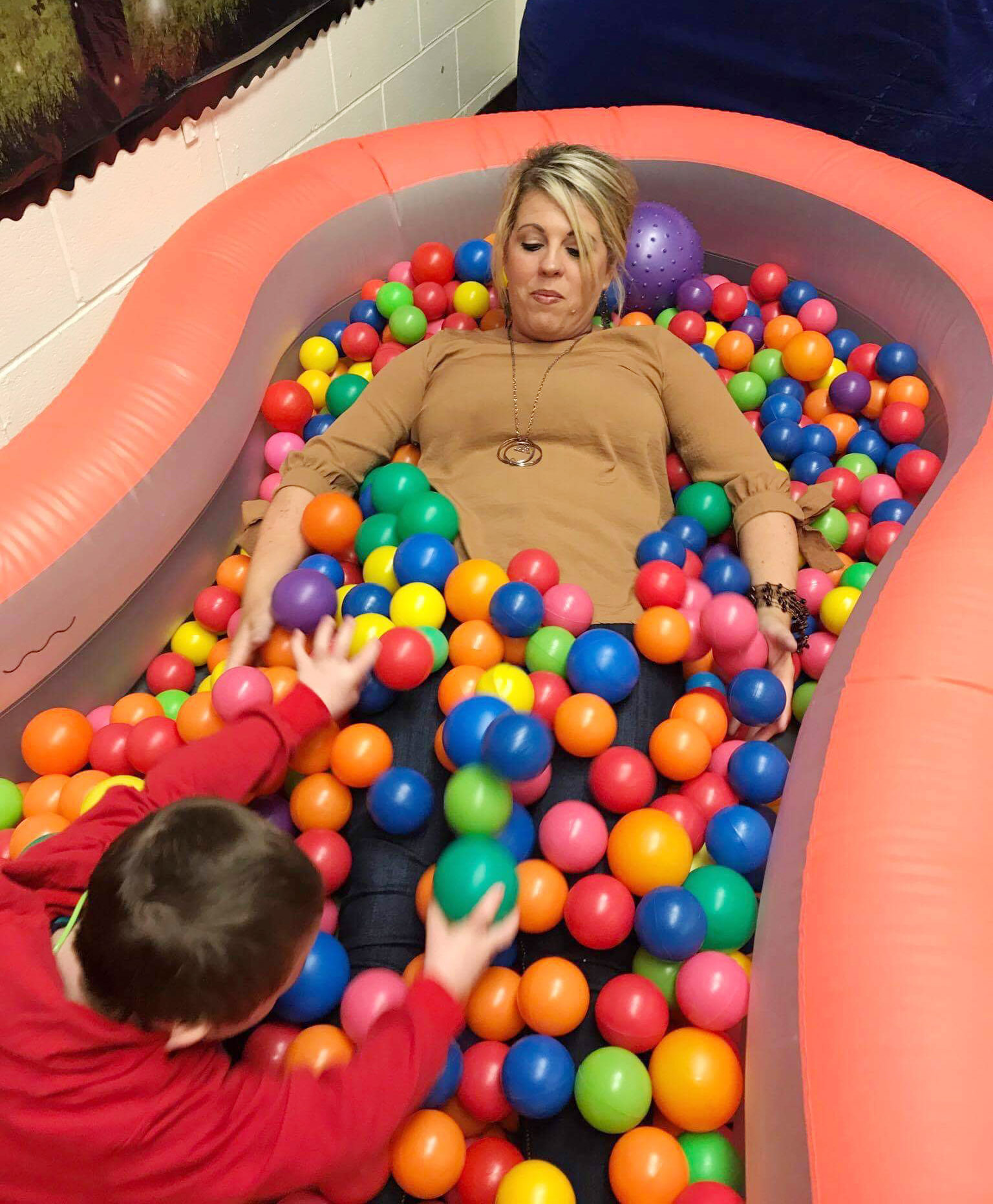CES Principal Elisha Rhodes plays ball with first-grader Nicholas Brunner in the ball pit.