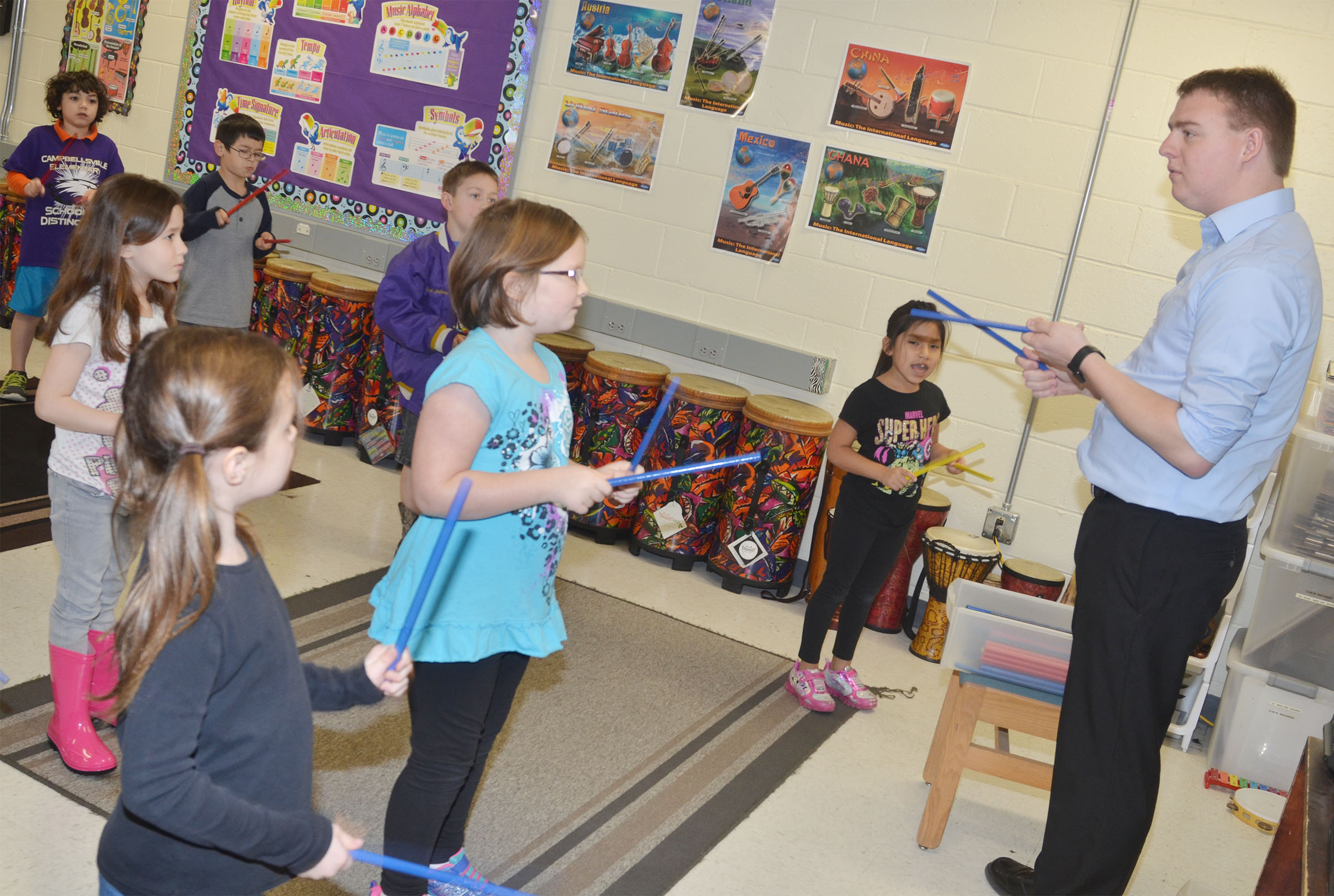 Lindsey Wilson College education student Tyler Cook teaches CES first-graders how to play the rhythm sticks.