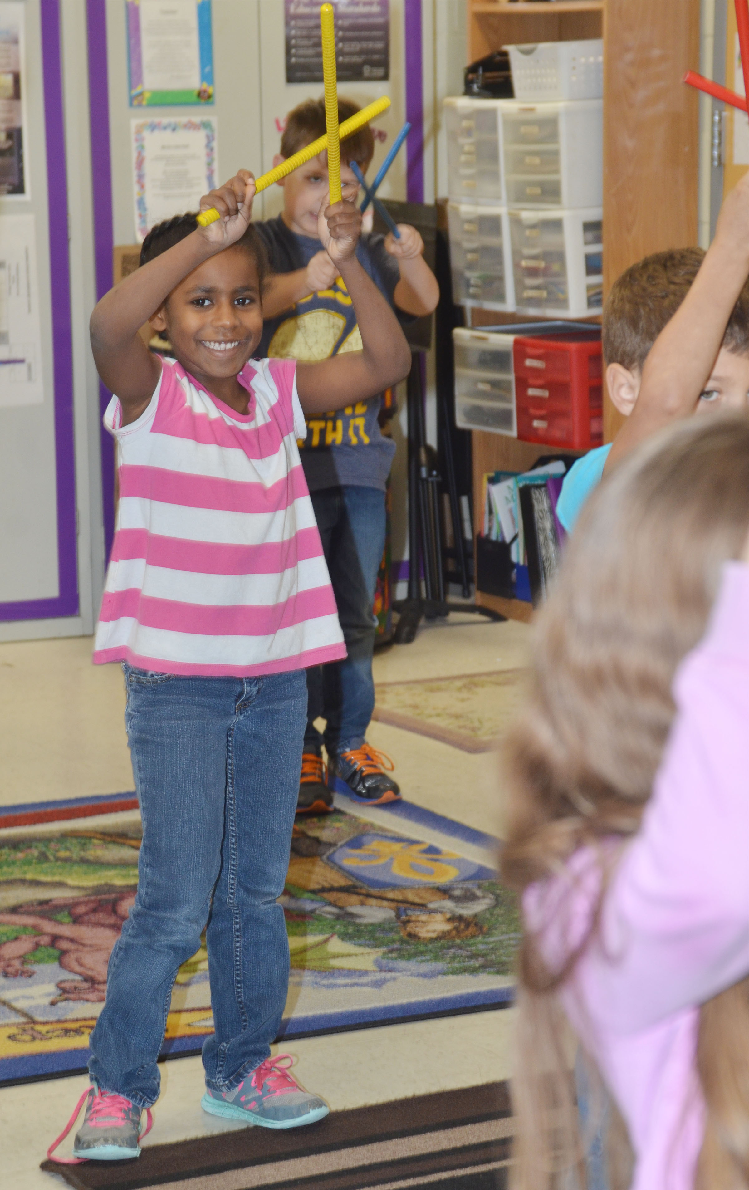 CES first-grader Destini Gholston plays the rhythm sticks.