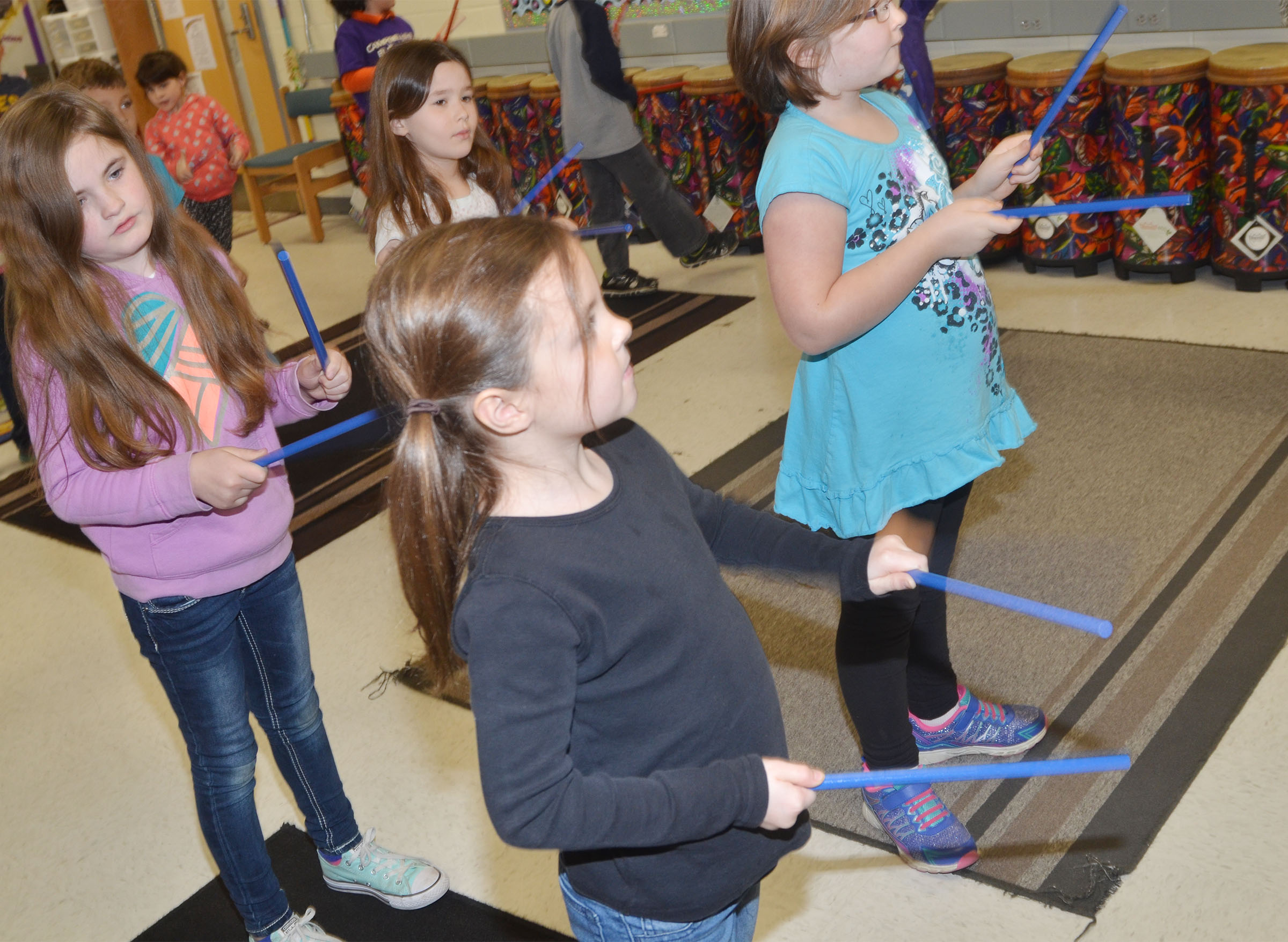 CES first-graders, in front, Molly Wolford, at left, and Justice Albrecht play the rhythm sticks with their classmates.
