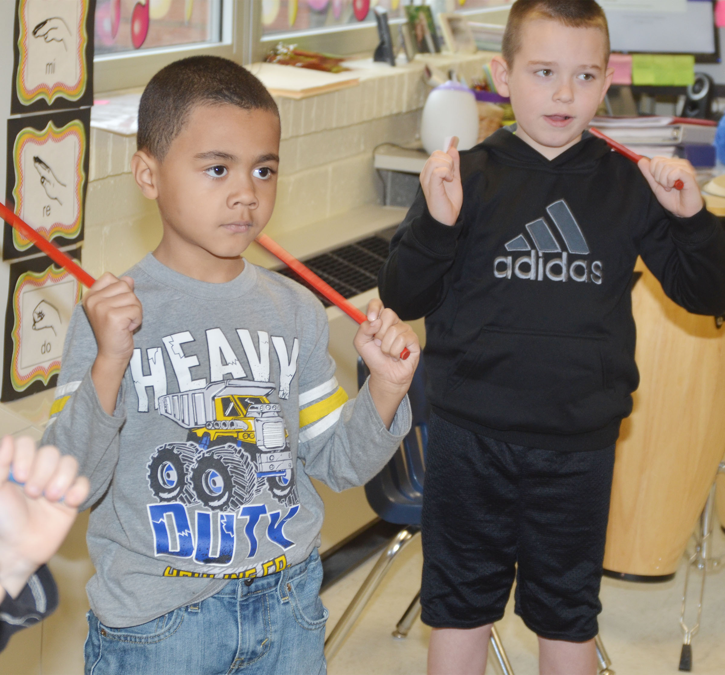 CES first-graders Trace Richardson, at left, and Colton Maggard play the rhythm sticks.