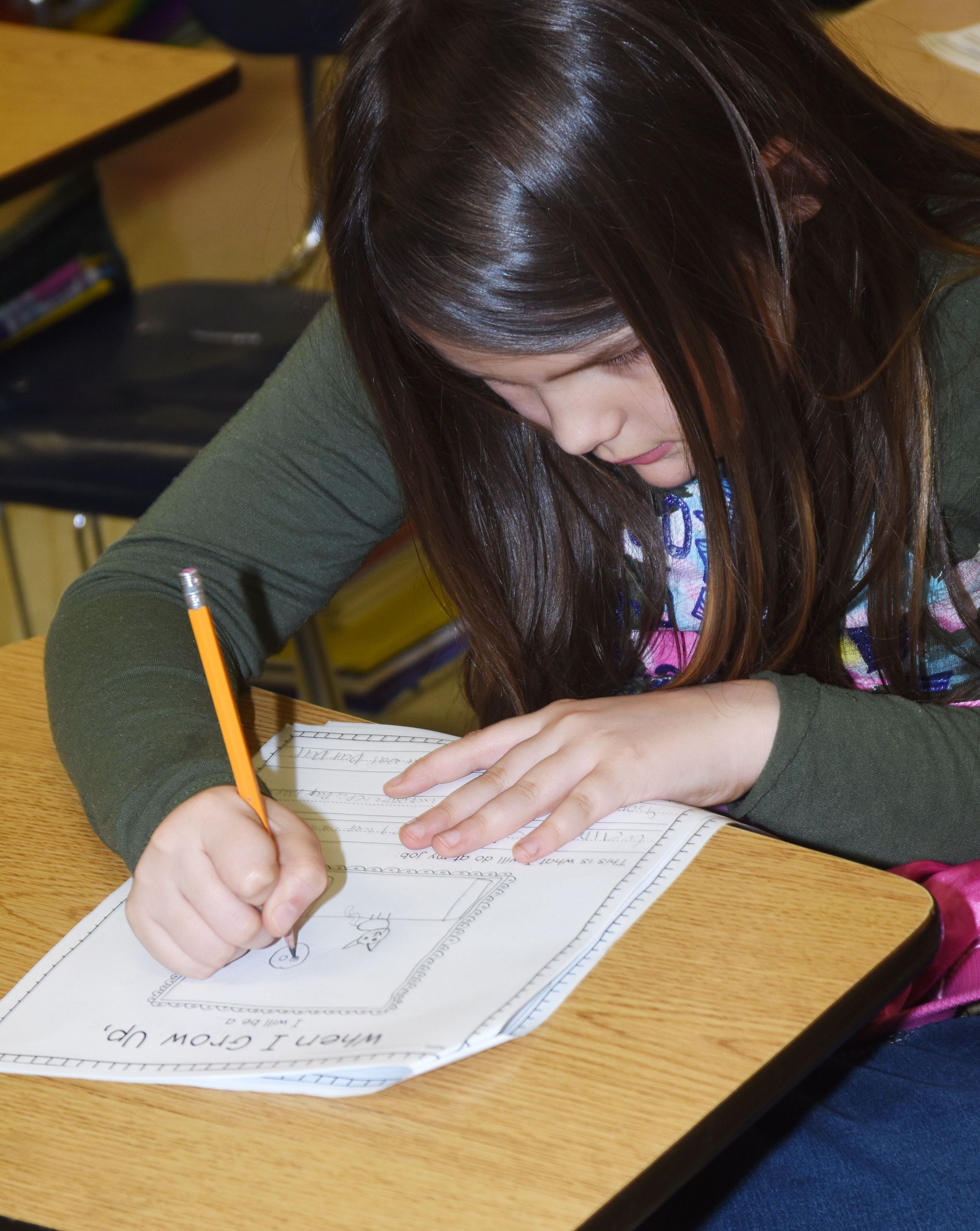 CES third-grader Dorothy Shively draws a picture of herself working at her future career.
