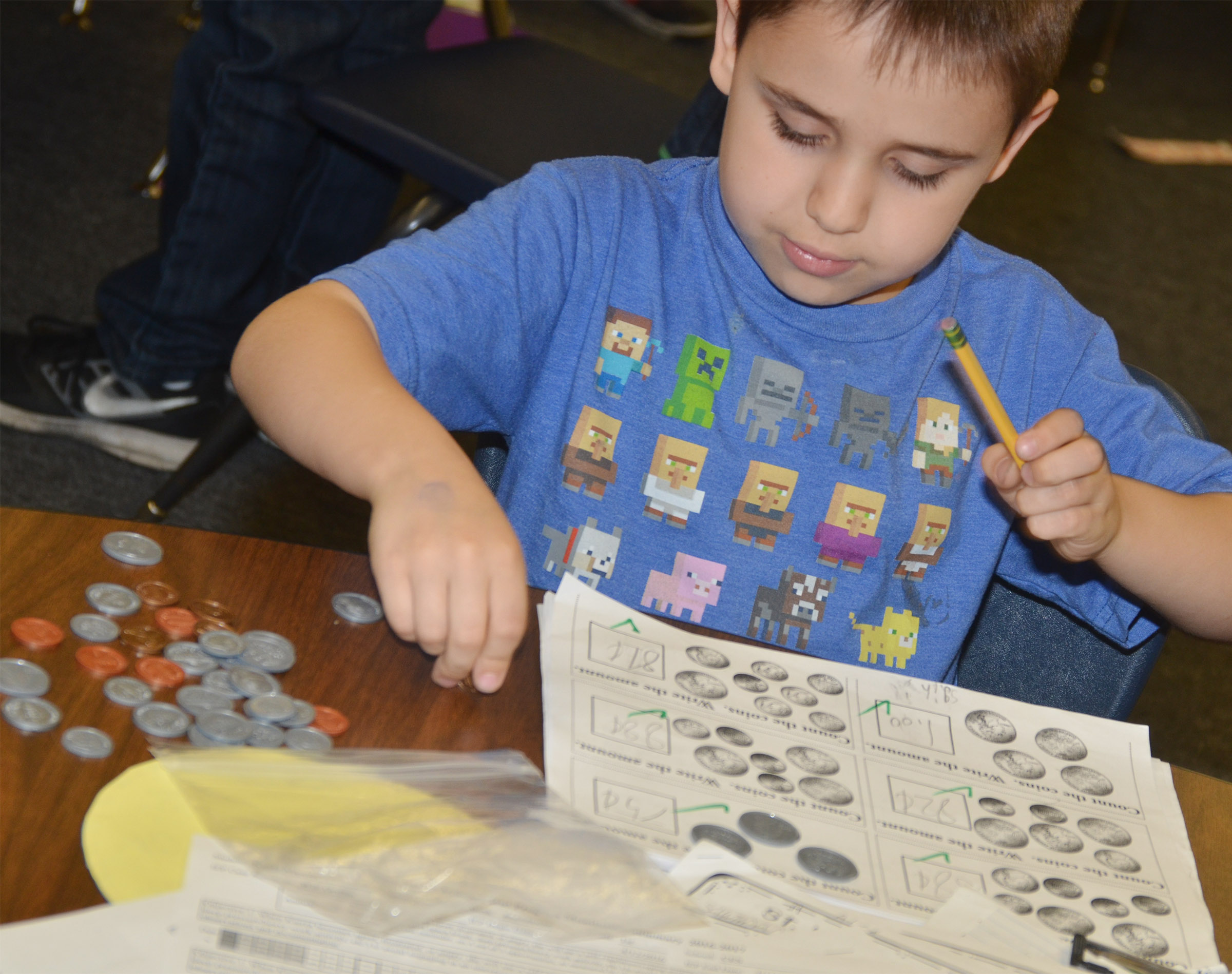 CES first-grader Aaron Floyd, who is taking a second-grade math class, practices counting coins.