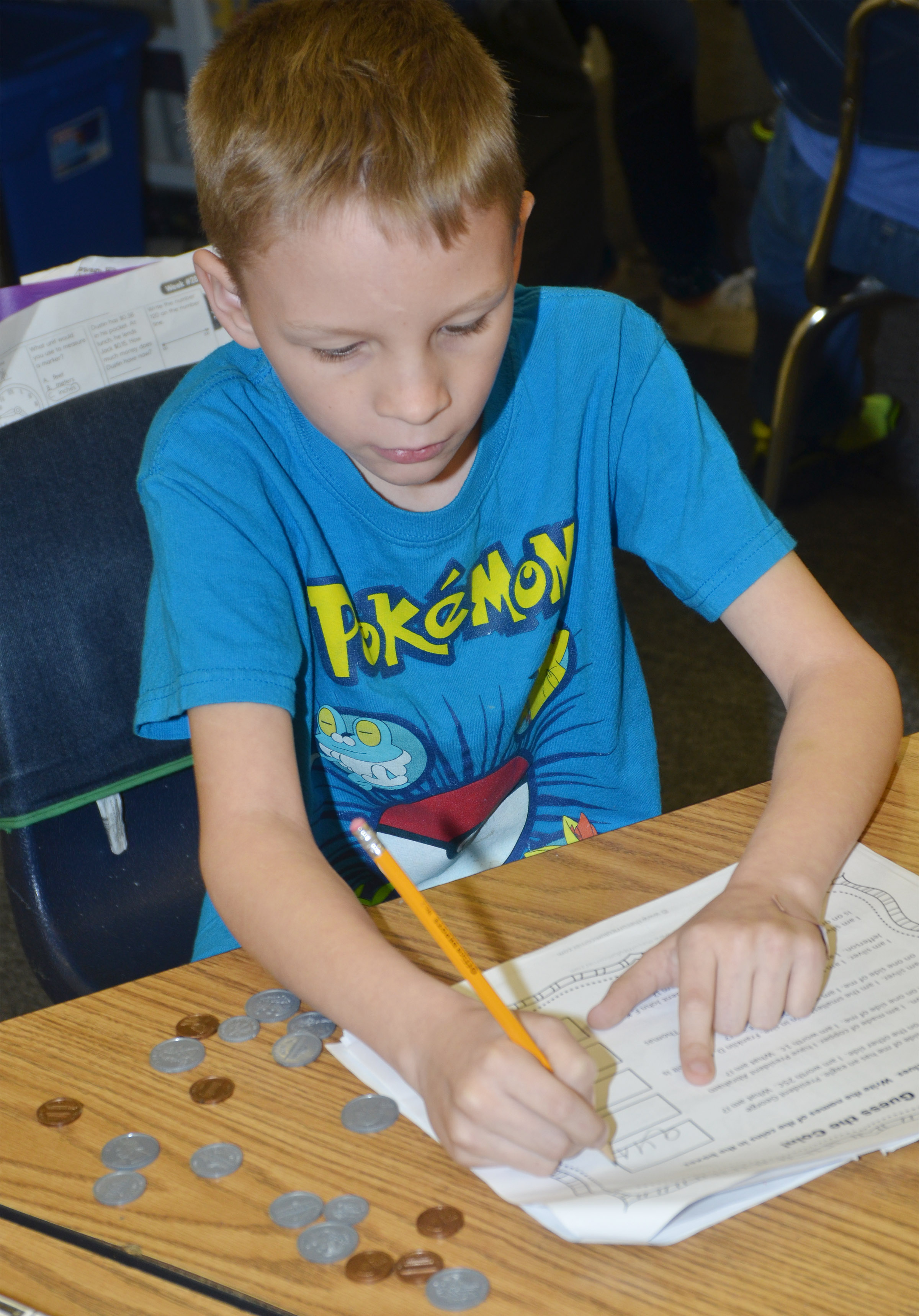 CES second-grader Braxton Agee practices counting money.