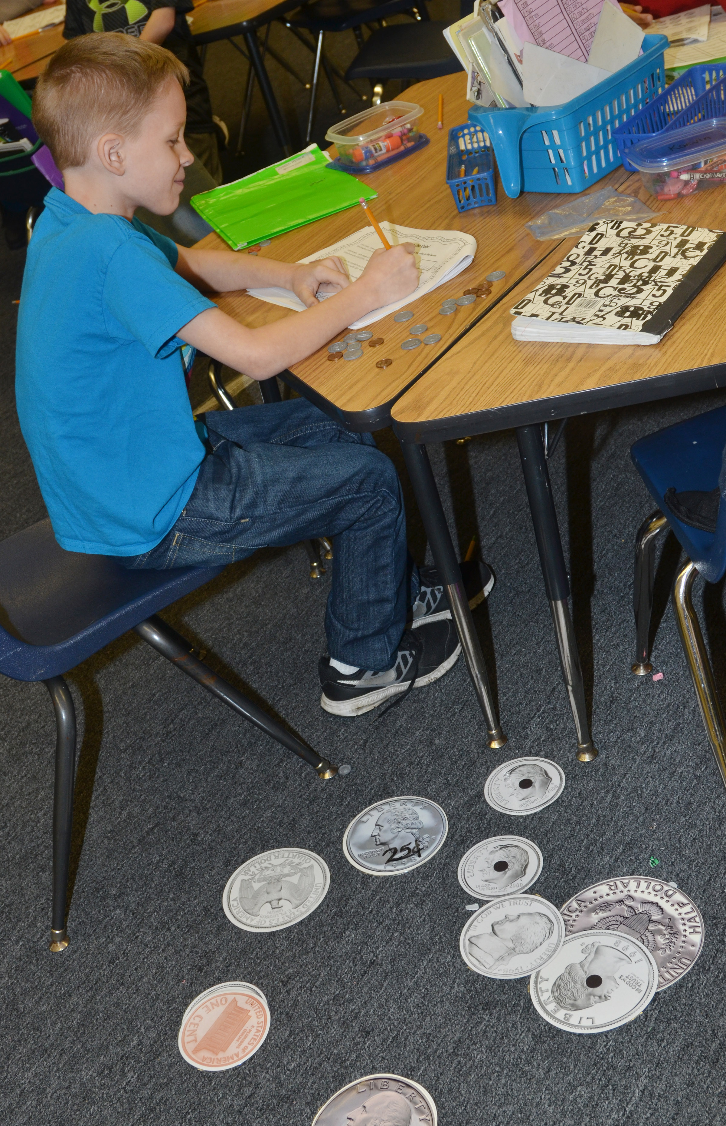 CES second-grader Braxton Agee uses large coins to count money.
