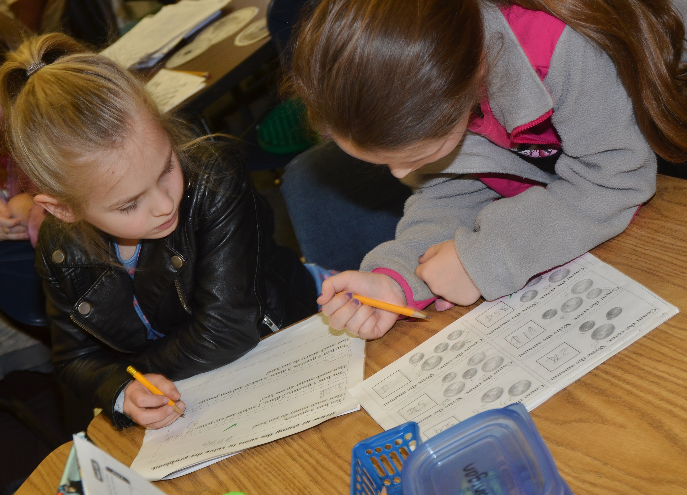 CES second-graders Ava Ellis, at left, and Keely Rakes help each other count money.