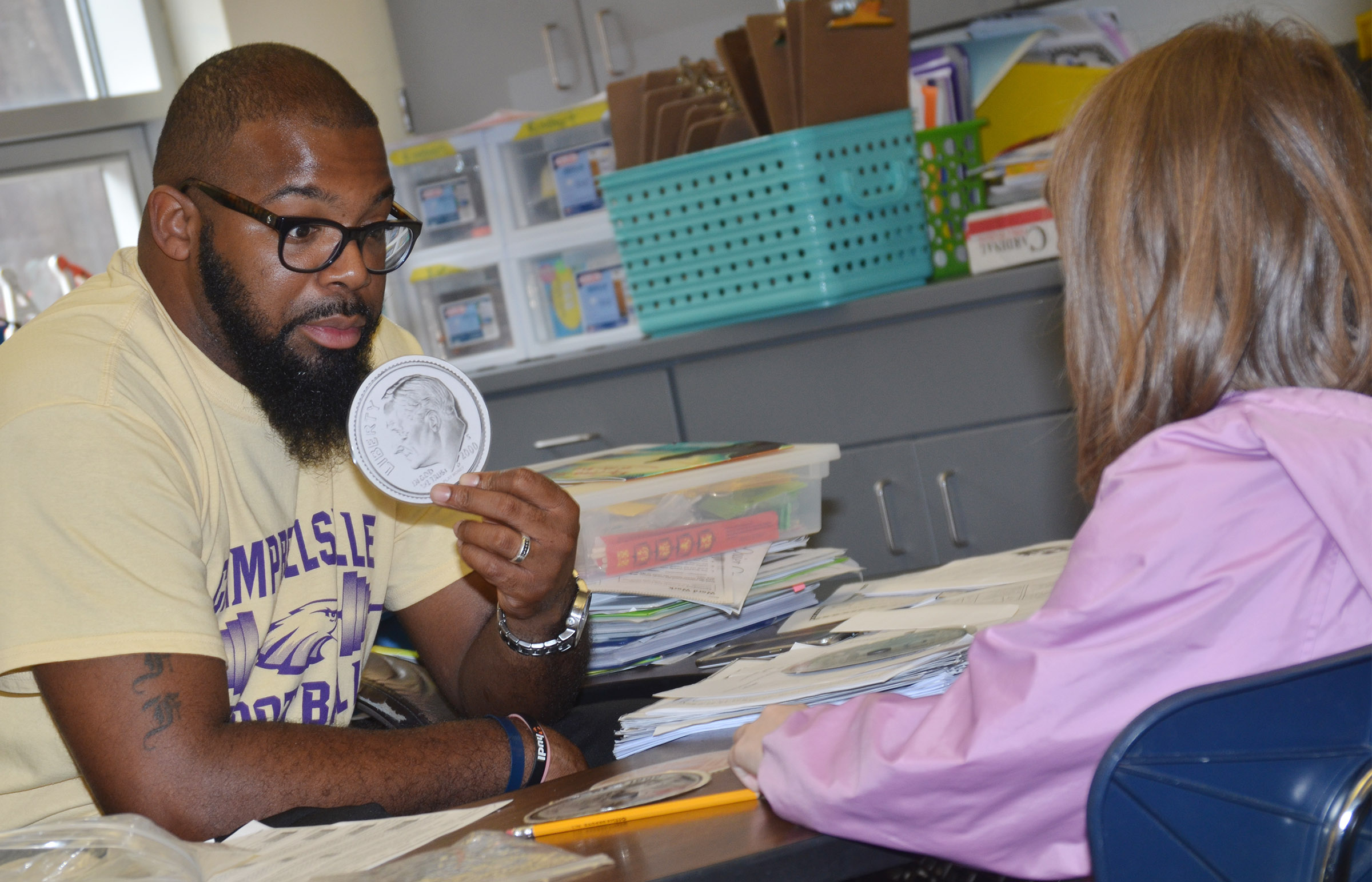 CES special education teacher Will Griffin helps second-grader Sammantha Wooley count money.