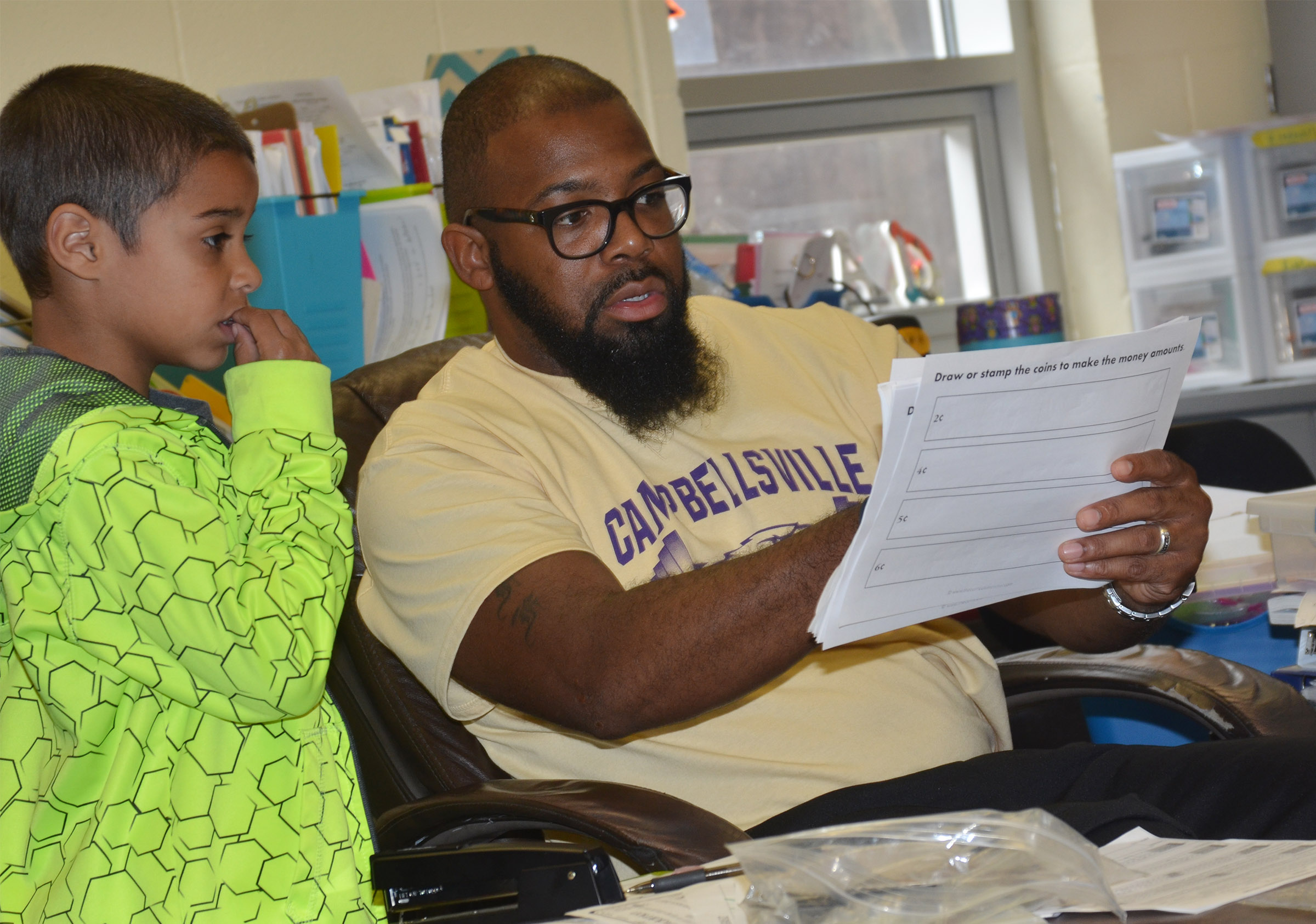 CES special education teacher Will Griffin helps second-grader Keylan Strong count money.