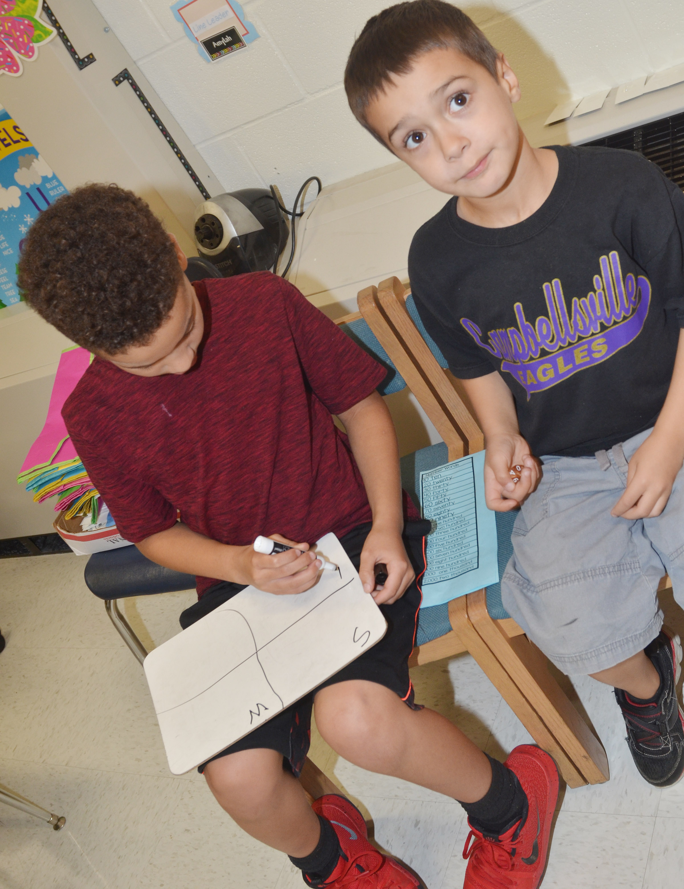 CES second-graders Bryant Mayo, at left, and Brenden Chastain practice writing number forms.