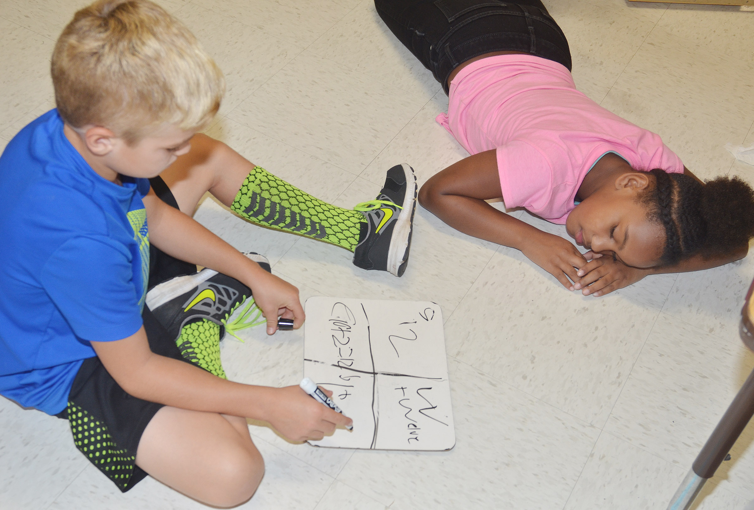 CES second-graders Dax Gray, at left, and Aliyandra Dunn practice writing number forms.