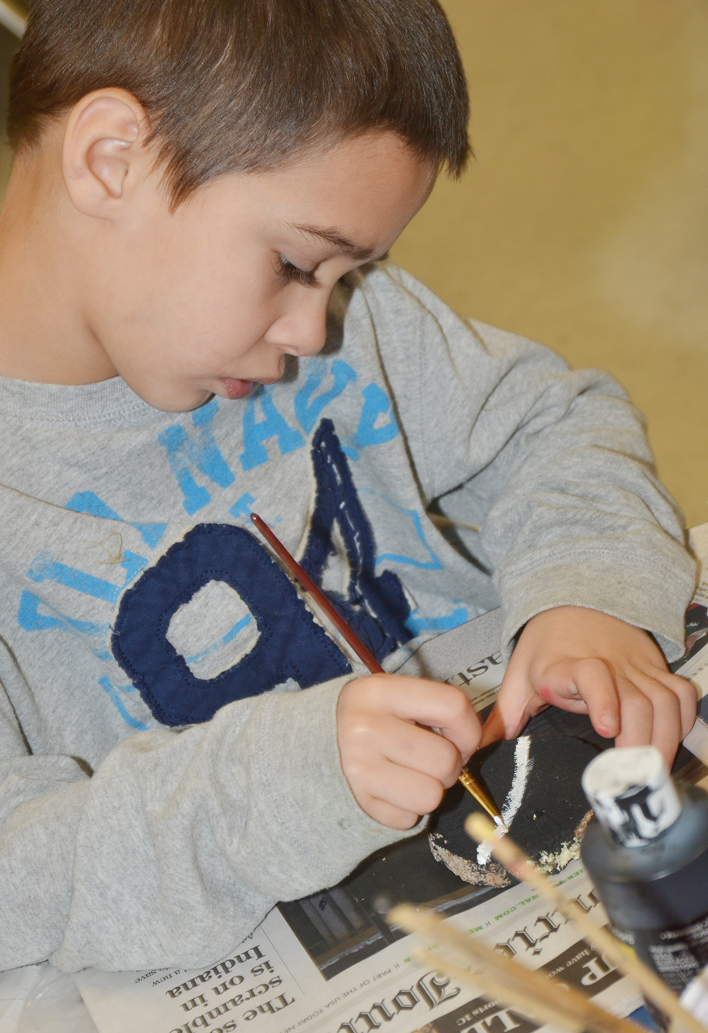 CES second-grader Brenden Chastain paints designs on his ornament.