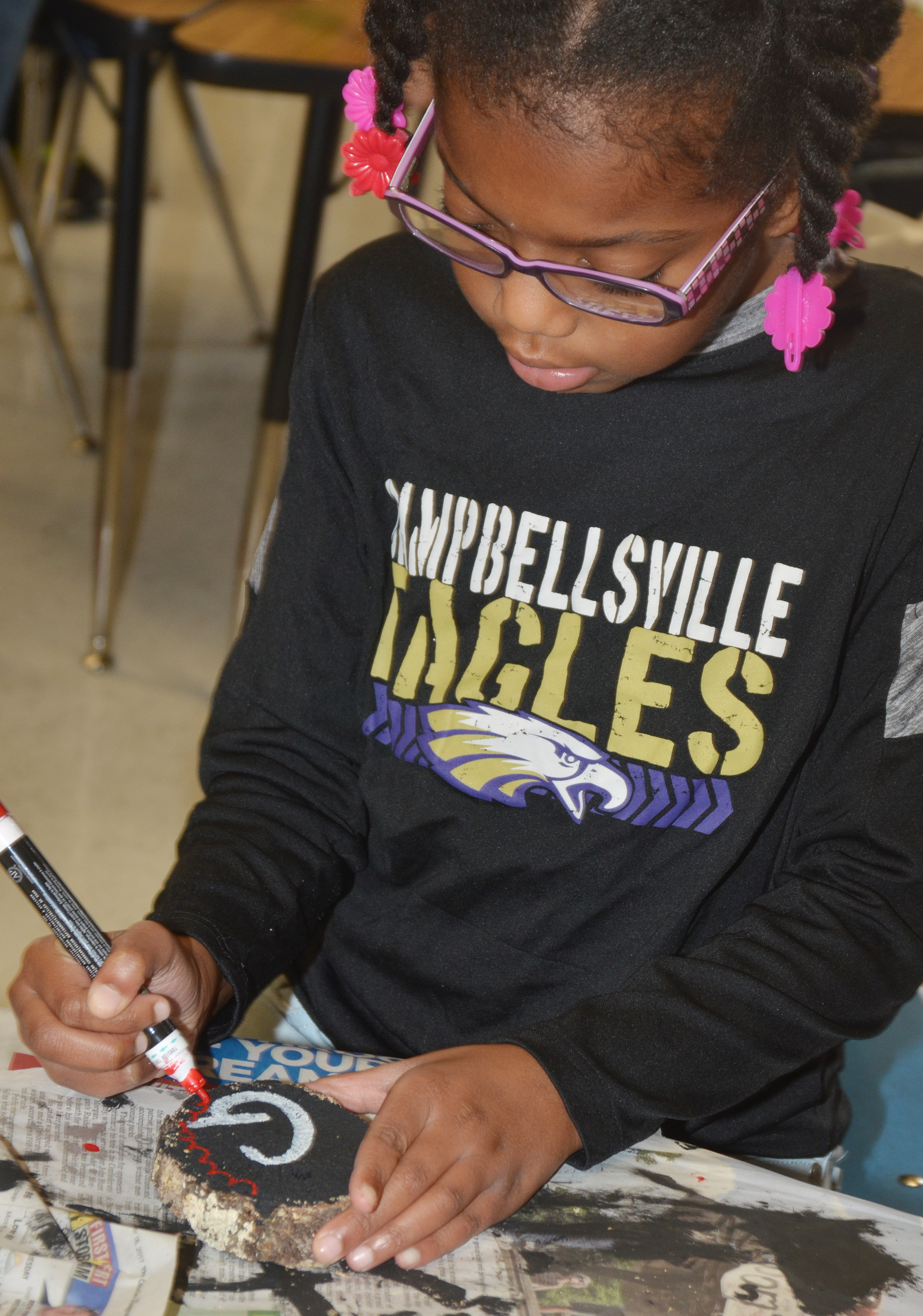 CES second-grader Willow Griffin paints designs on her ornament.