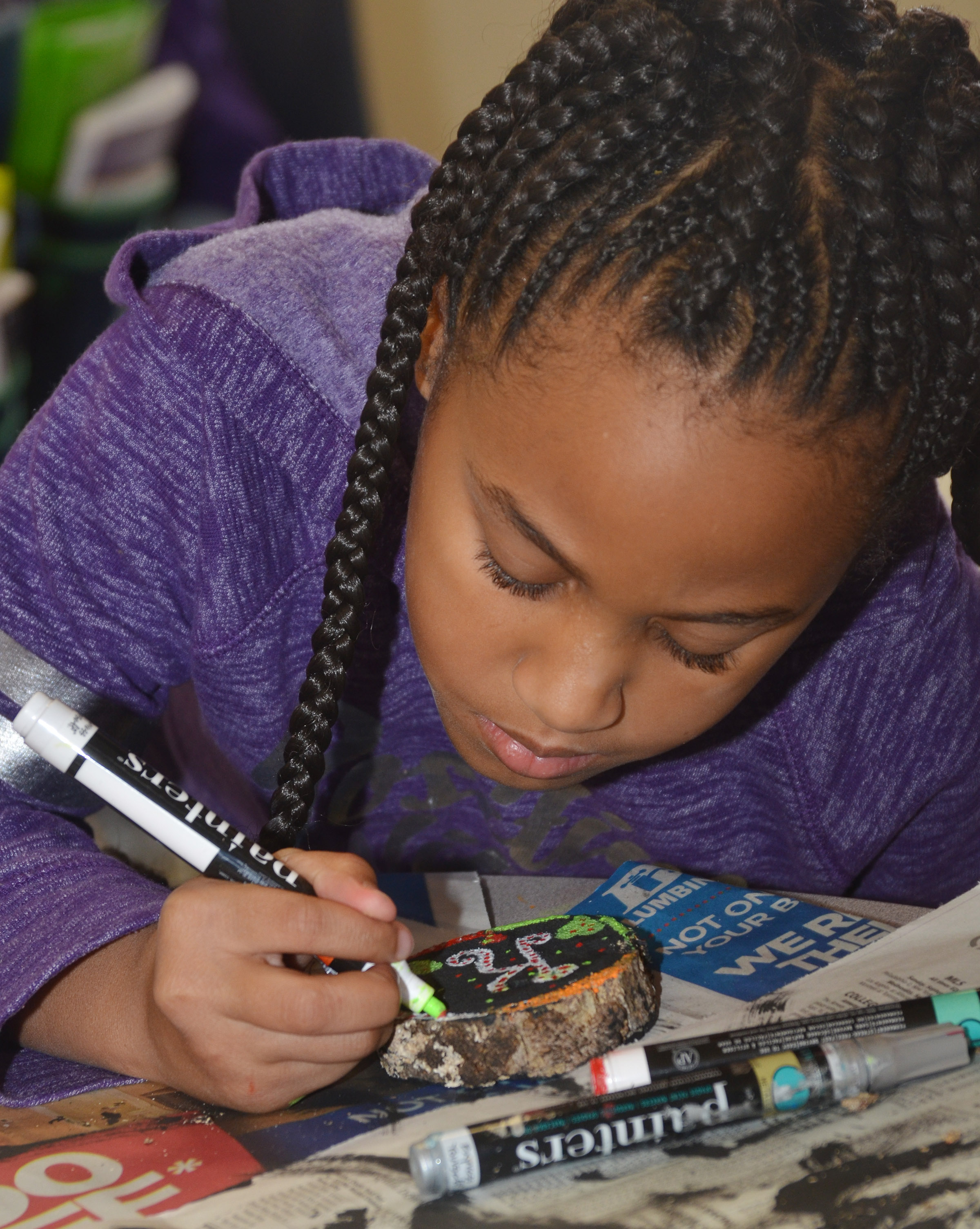 CES second-grader Kadance Ford paints designs on her ornament.