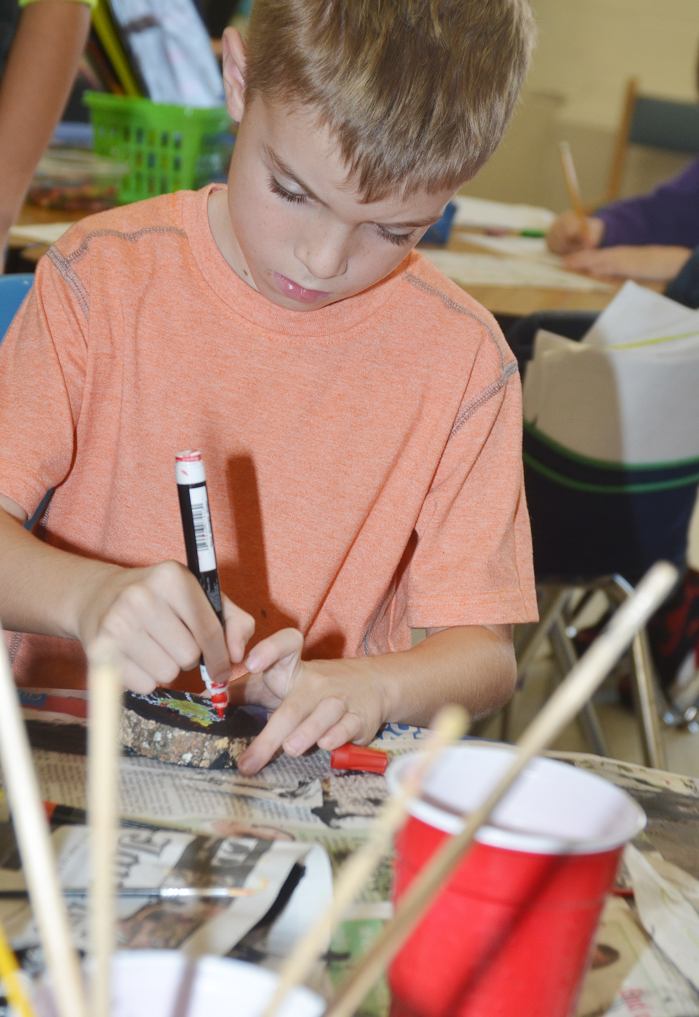 CES second-grader Ben Lord paints designs on his ornament.