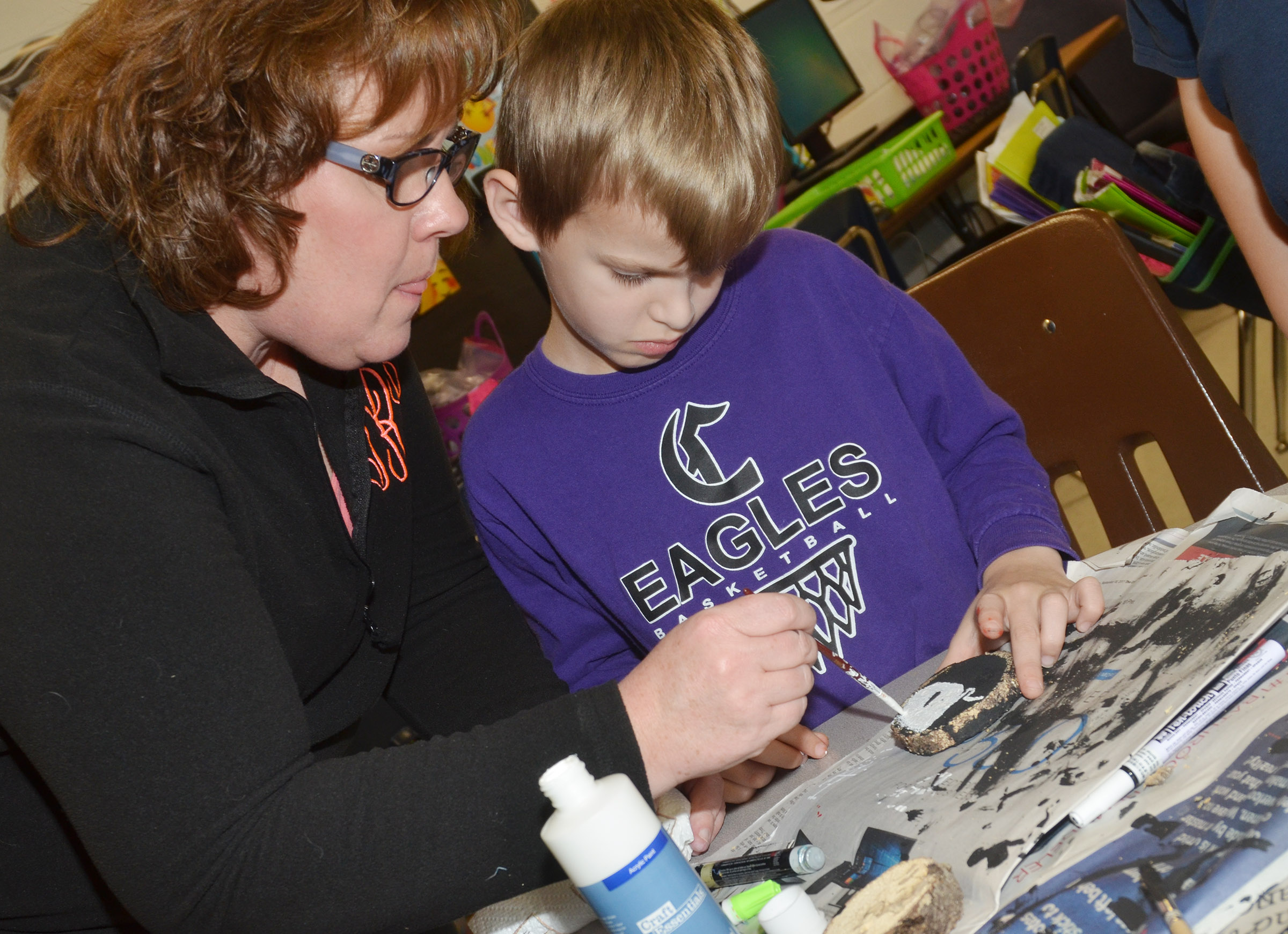 CES second-grade teacher Tracey Rinehart helps Logan Weddle paint a snowman on his ornament.