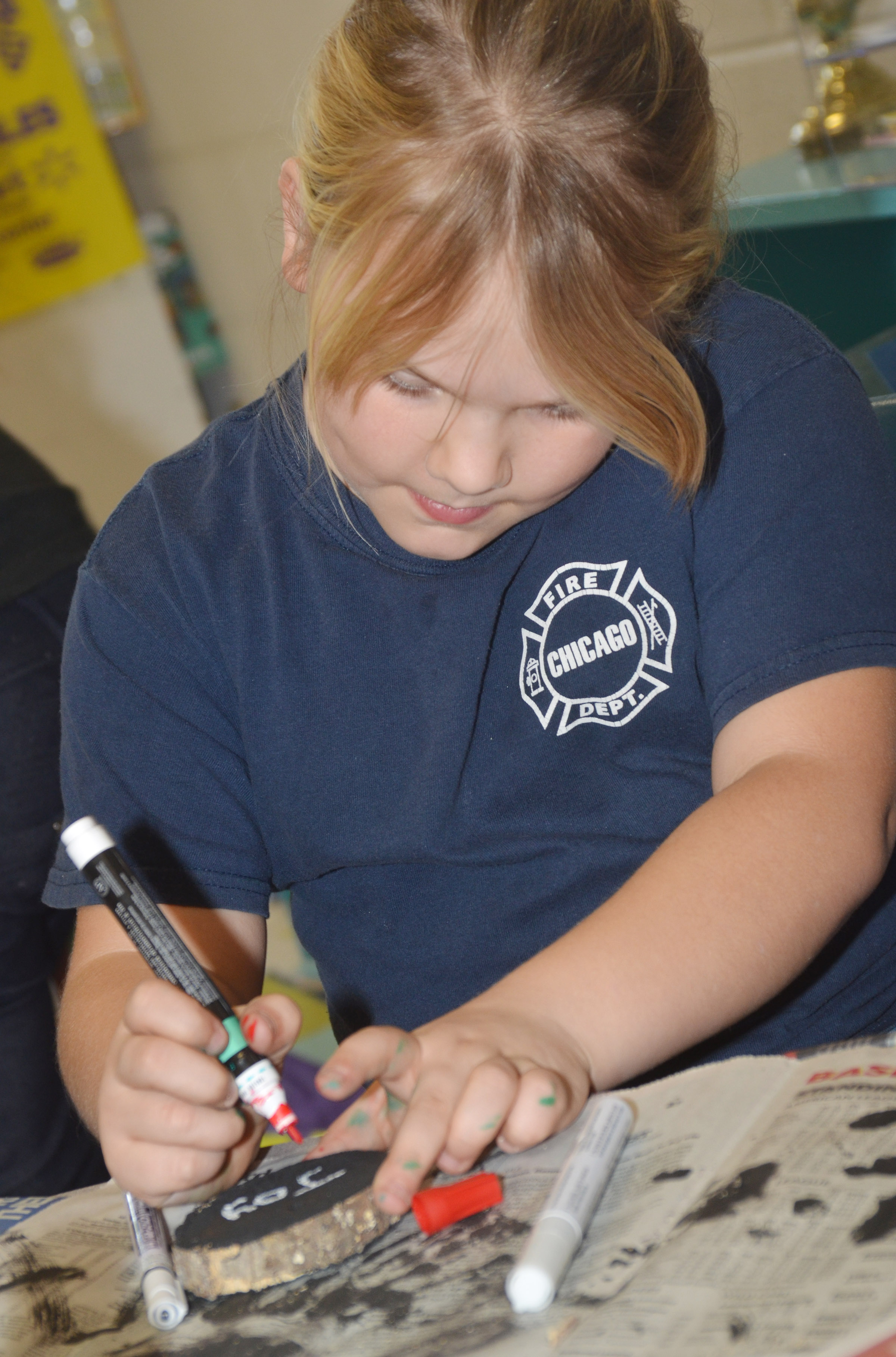 CES second-grader Addysen England draws designs on her ornament.