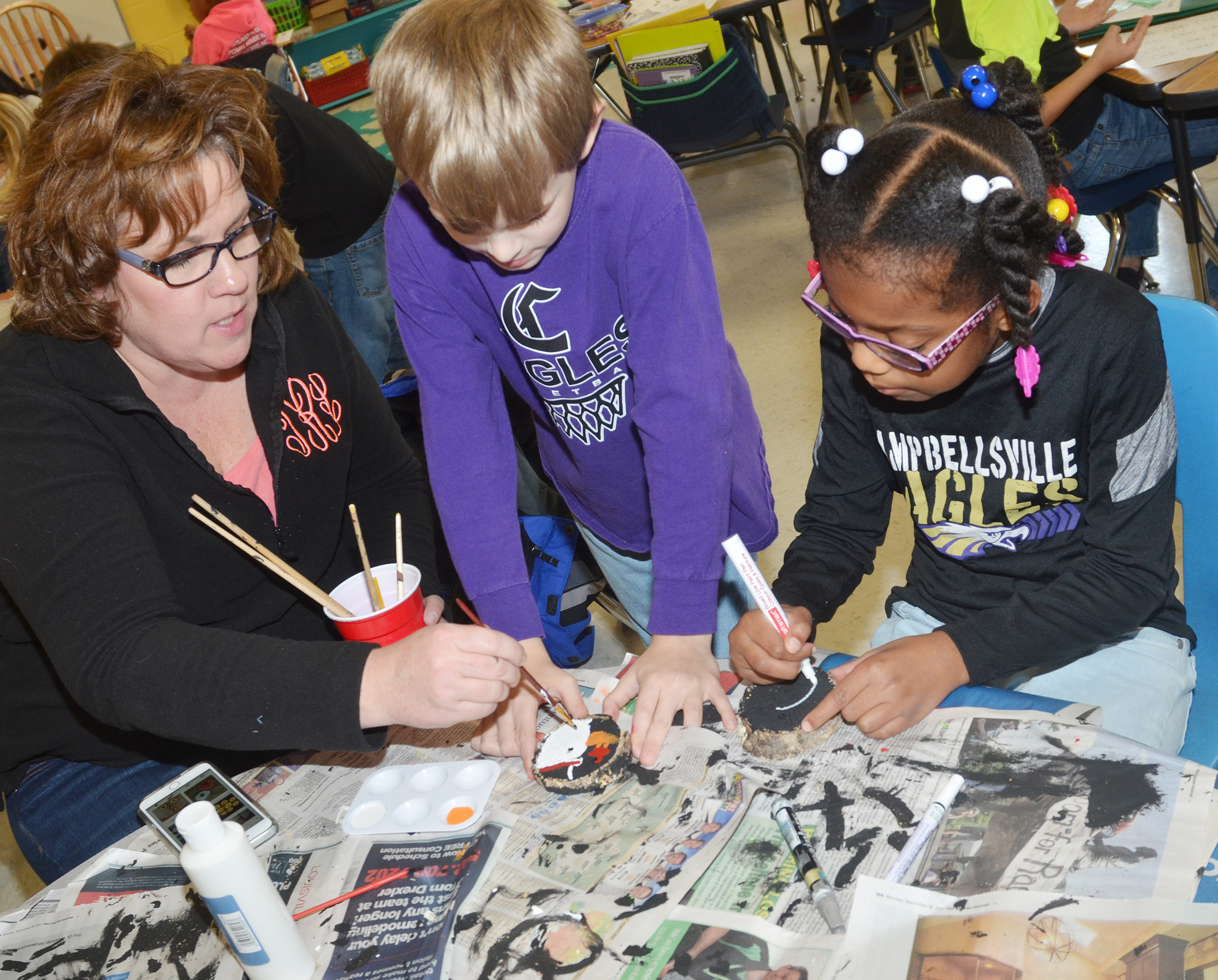 CES second-grade teacher Tracey Rinehart helps Logan Weddle and Willow Giffin create their ornaments.