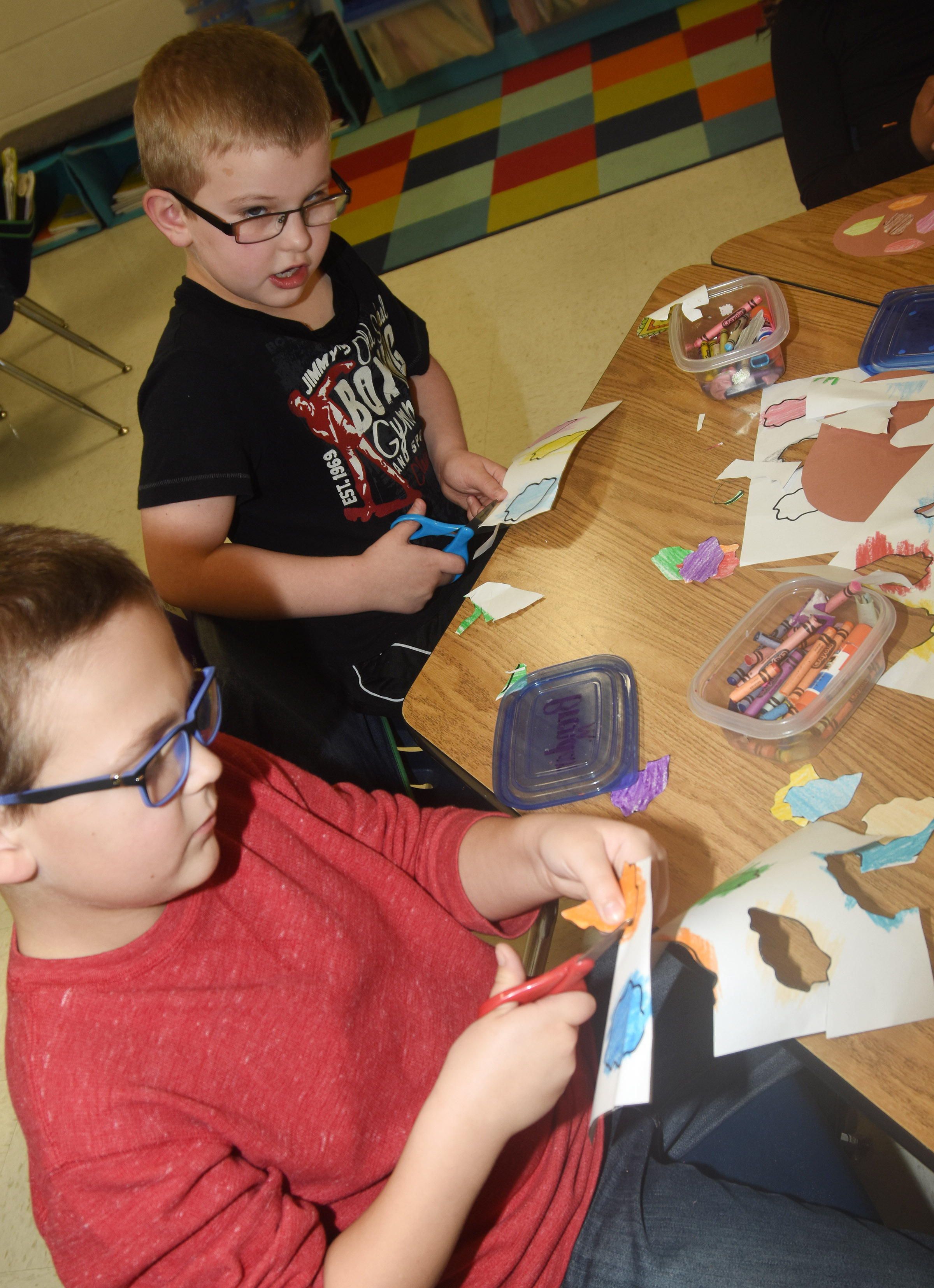CES second-graders Brendan Martin, at left, and Ethan Bailey cut out their paint splotches as they create their prefix palates.