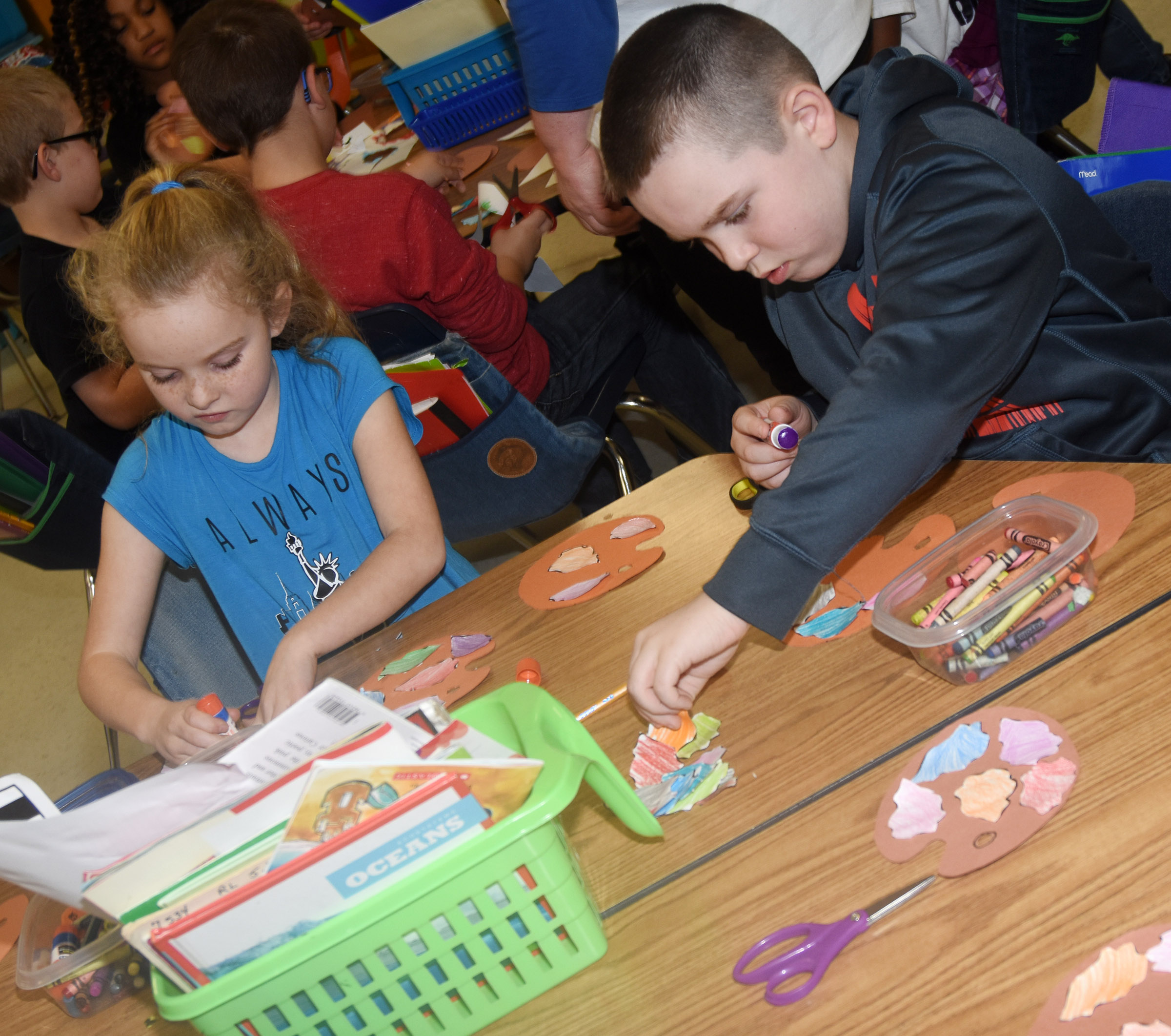 CES second-graders Katelynn Vest, at left, and Colton Maggard glue their paint splotches on their prefix palates.