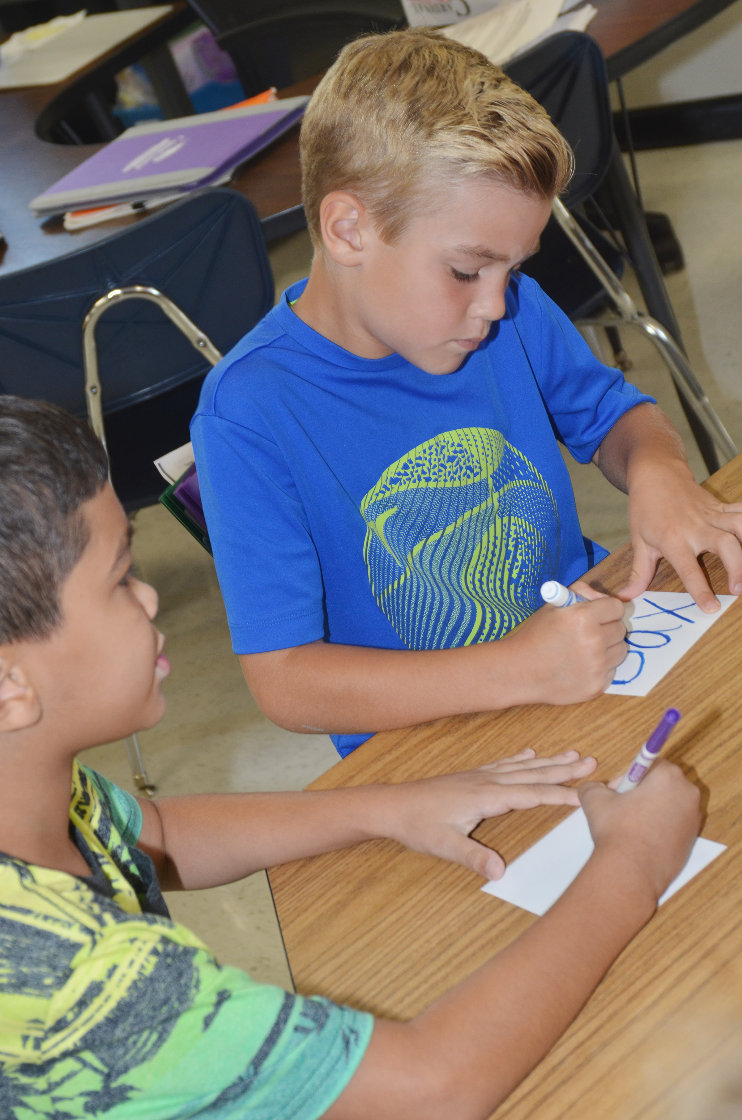 CES second-graders Xadrian Fugate, at left, and Dax Gray decorate their name tags for their book bags.