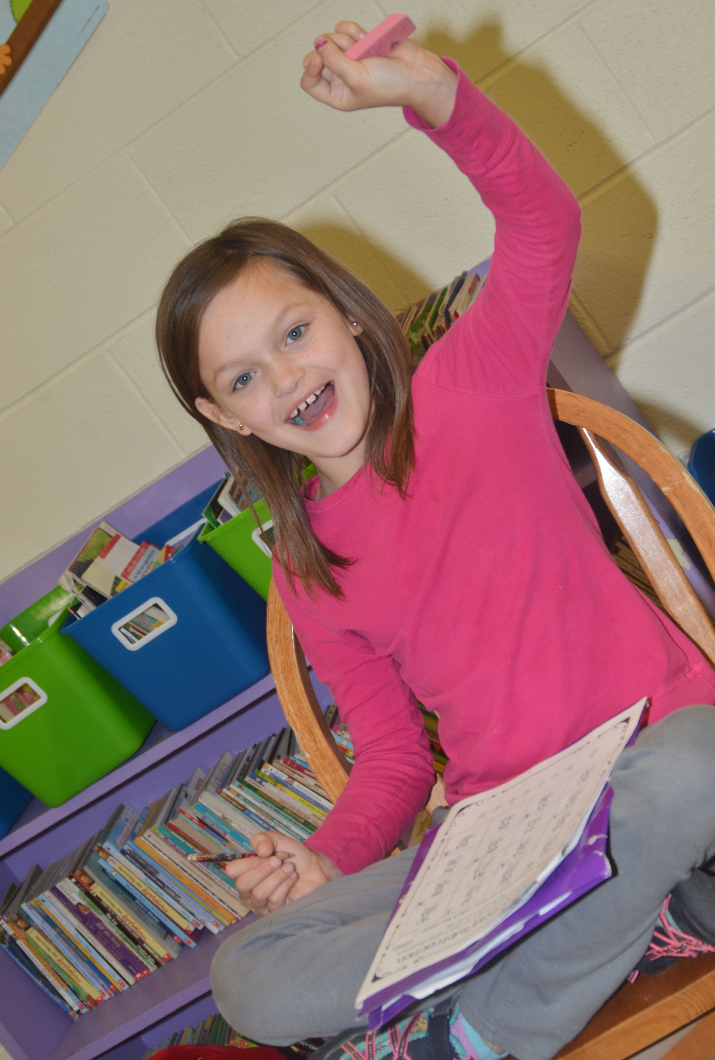 CES second-grader KayLee Lamer smiles as she works her St. Patrick's Day math worksheet.
