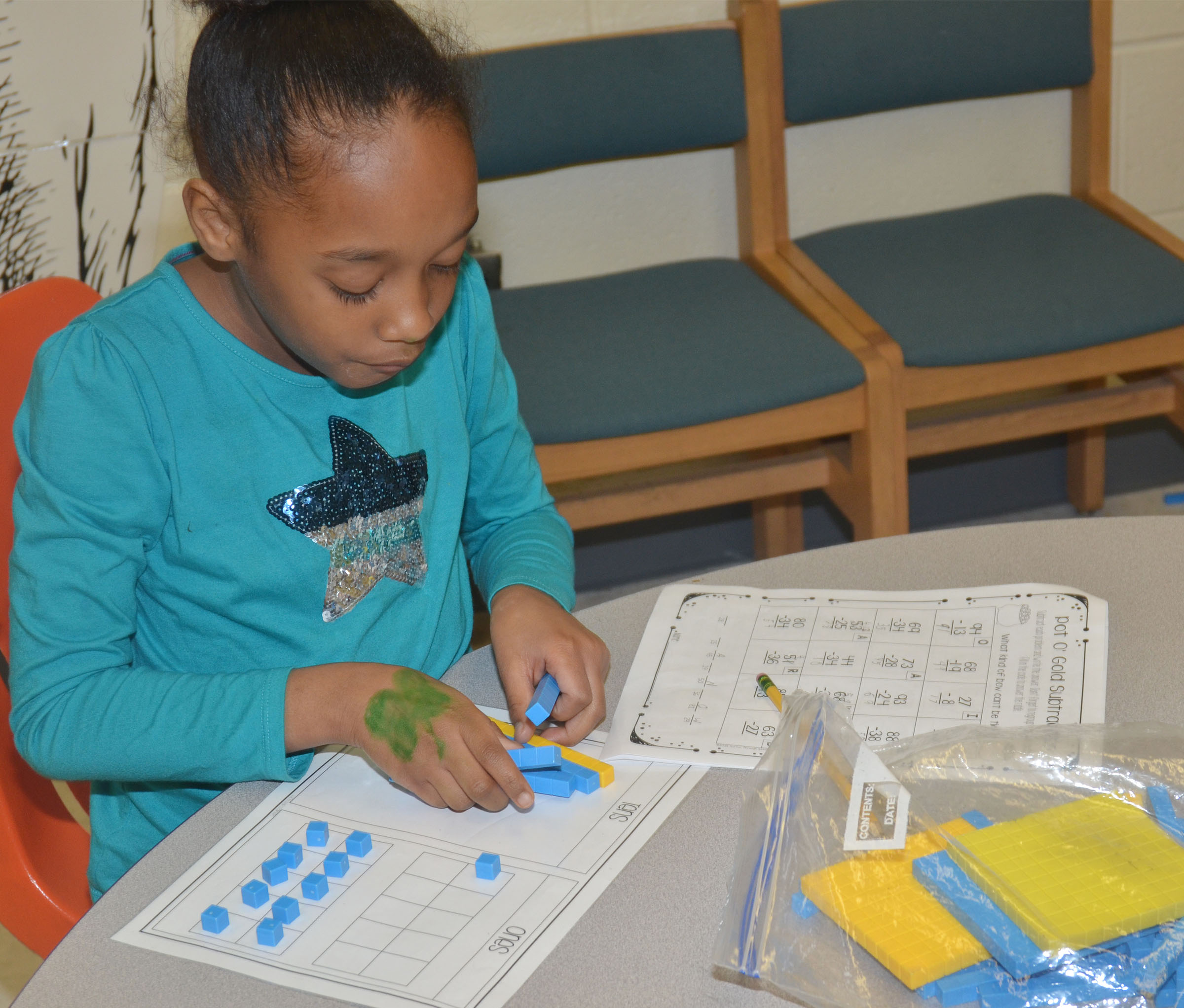 CES second-grader Lashonda Wilkinson uses blocks to help her work a St. Patrick's Day math problem.
