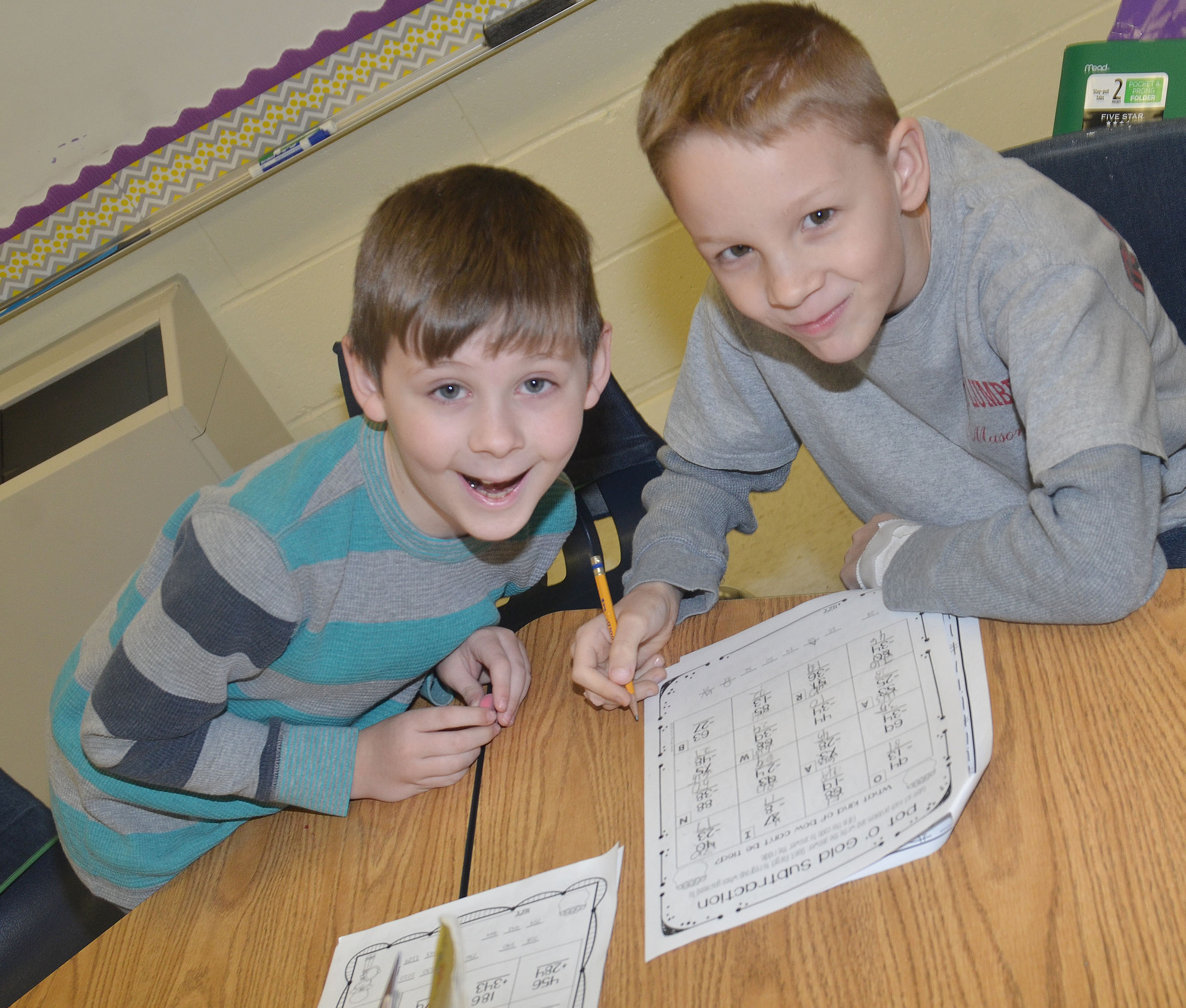 CES second-graders Ryan Tungate, at left, and Braxton Agee smile as they work a St. Patrick's Day math problem together.