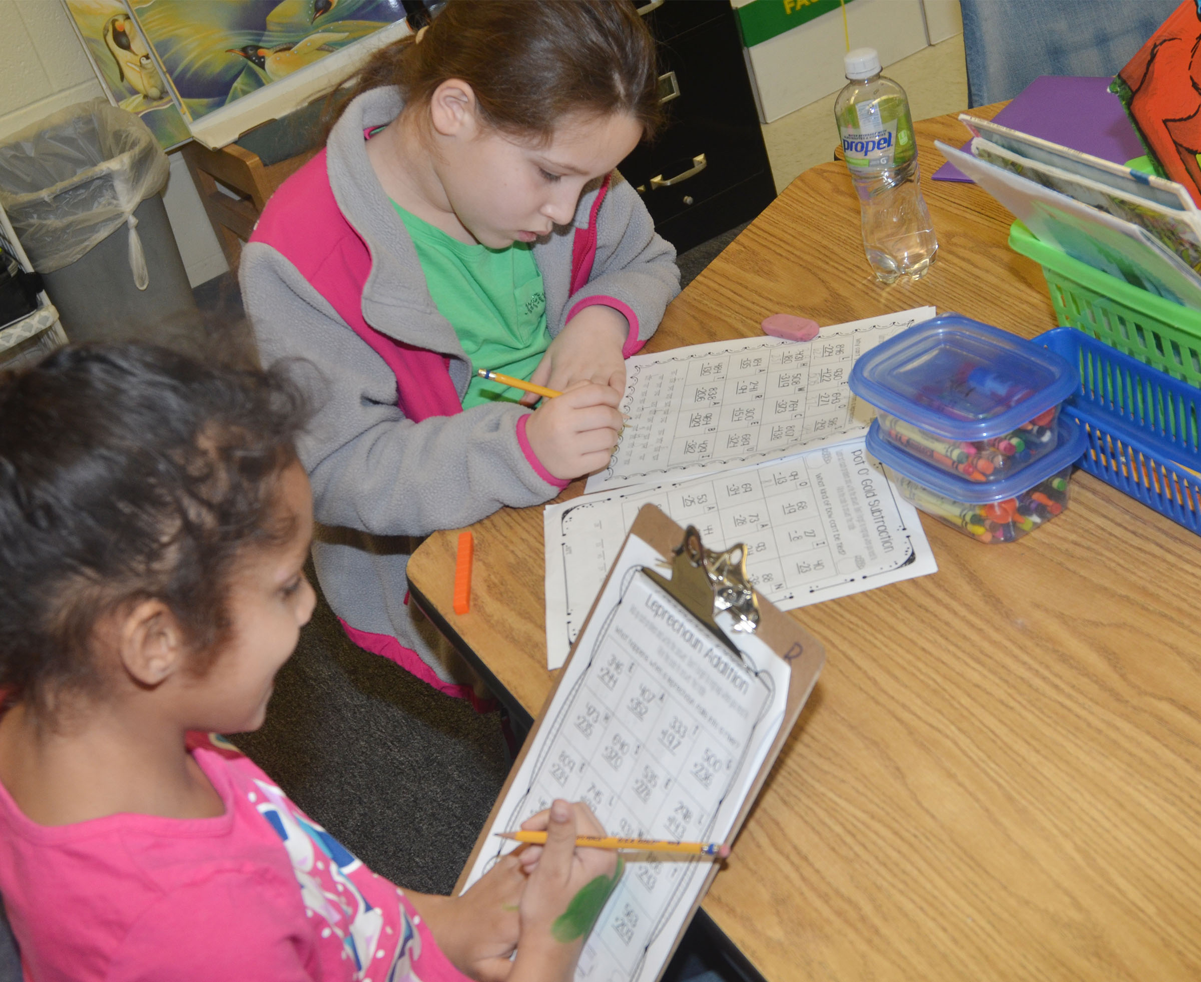 CES second-graders Malia Thompson, at left, and Keely Rakes work St. Patrick's Day math problems together.