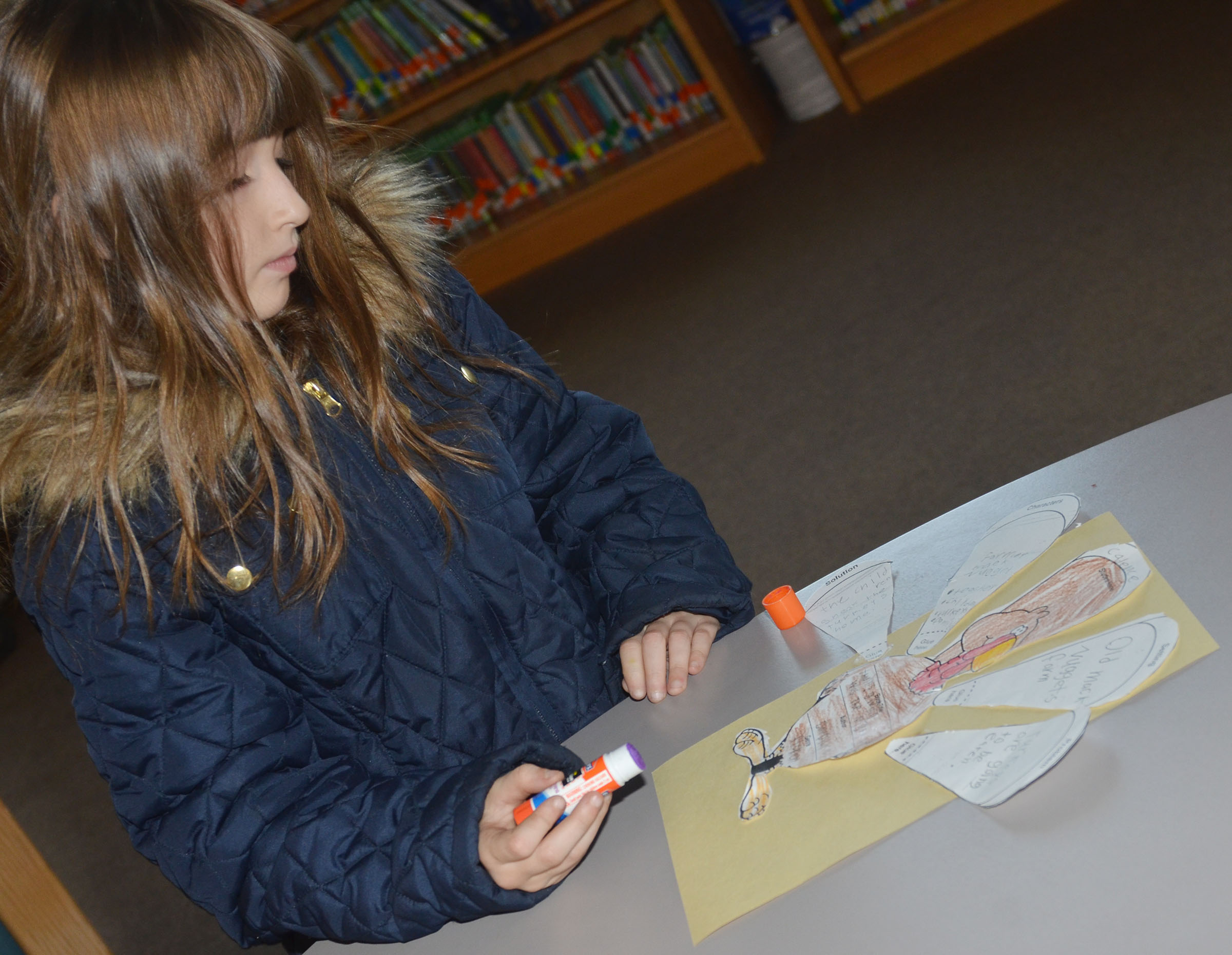 CES second-grader Cadence Burton glues her turkey to construction paper.