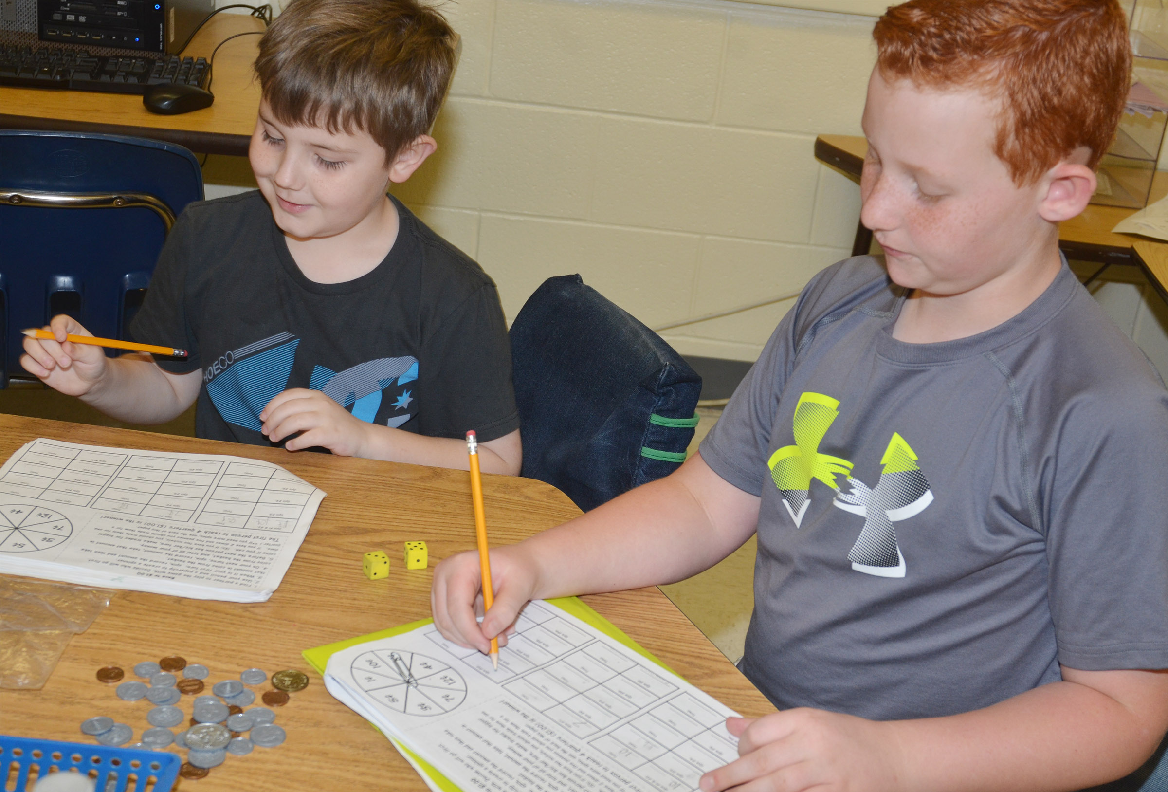 CES second-graders Seamus Huber, at left, and Reece Swafford play a game to see how well they can count money.