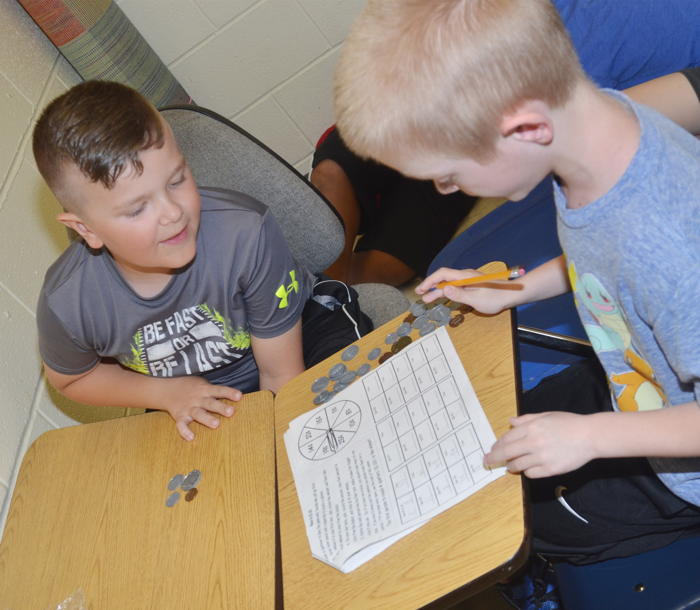 CES second-graders Cayton Lawhorn, at left, and Evan Cundiff play a game to see how well they can count money.