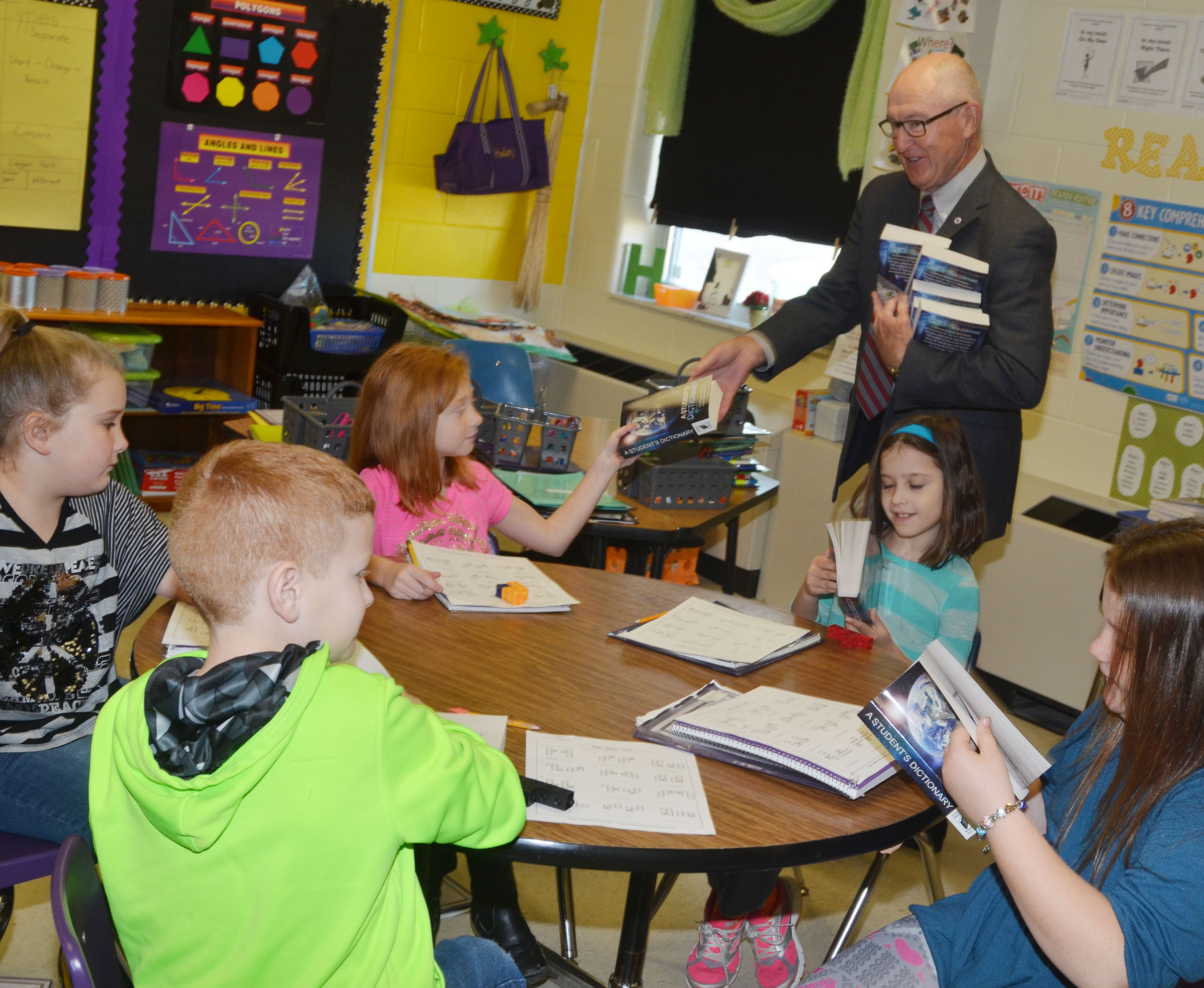 Campbellsville Rotary Club member Chuck Vaughn passes out dictionaries to CES third-grade students.