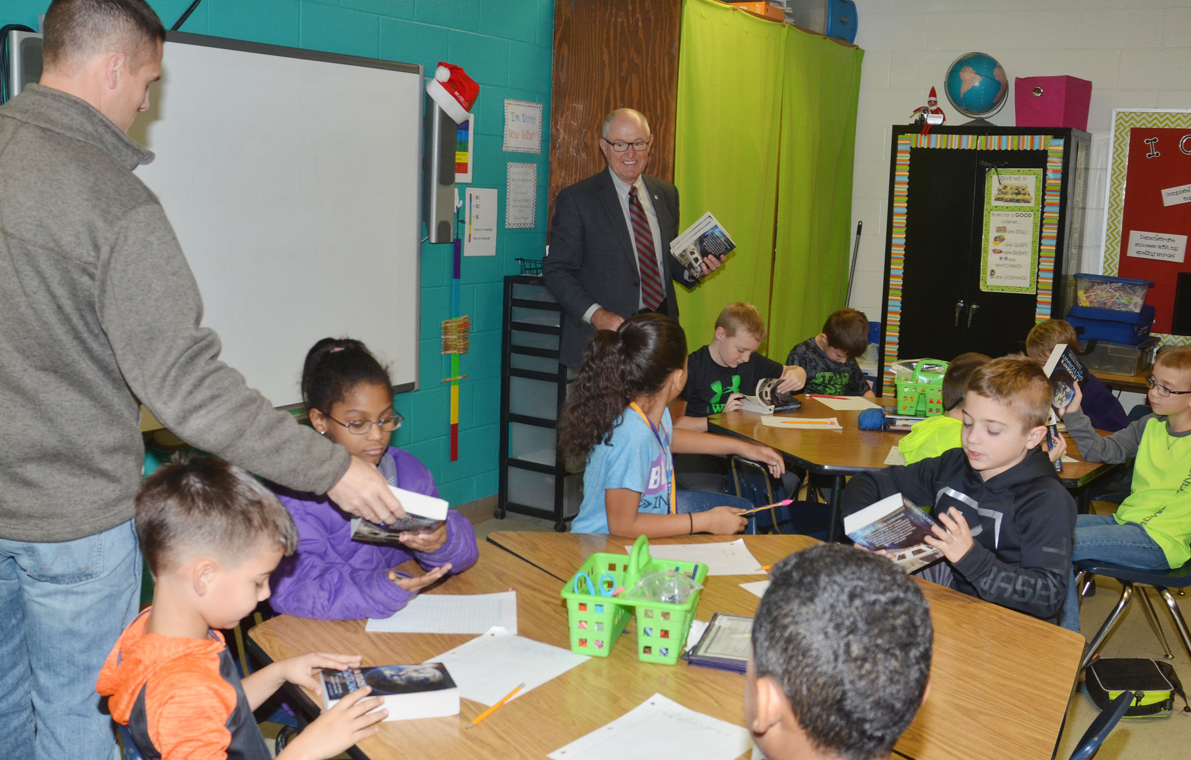 Campbellsville Rotary Club members Clark Howard, at left, and Chuck Vaughn pass out dictionaries to CES third-grade students.