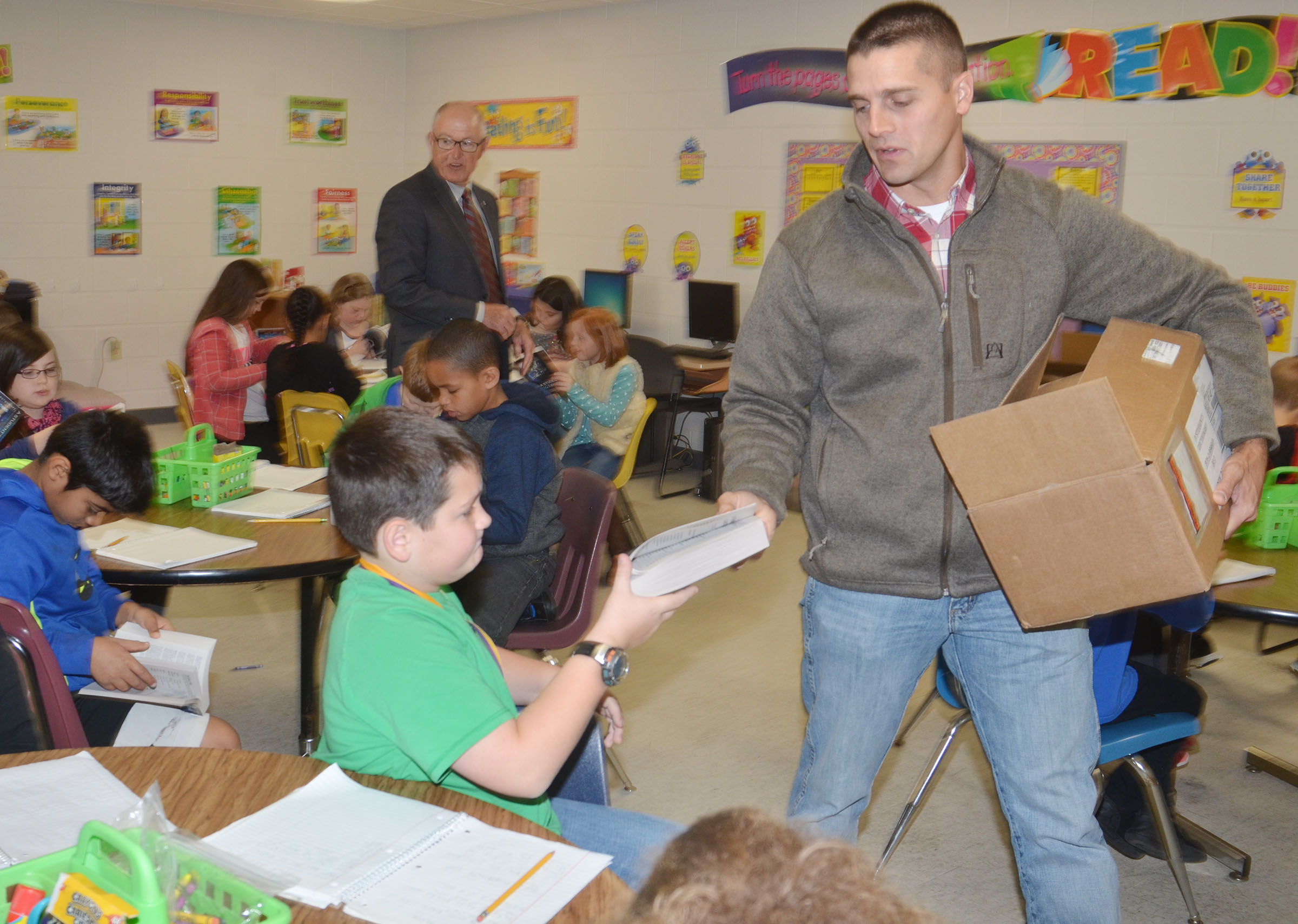 Campbellsville Rotary Club member Clark Howard passes out dictionaries to CES third-grade students.