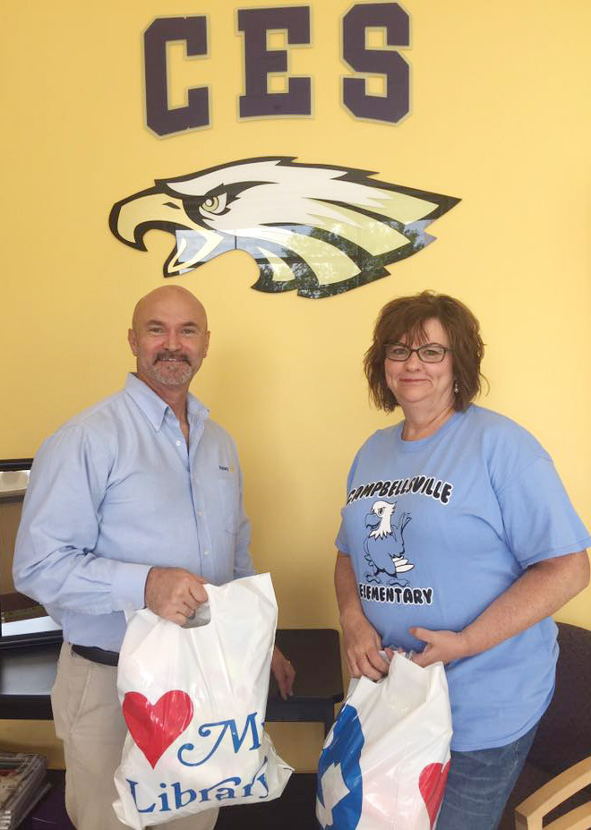 Susan Kennon, a Campbellsville Family Resource and Youth Services Center liaison at CES, accepts a donation of underwear from Campbellsville Rotary President Les Chadwick.