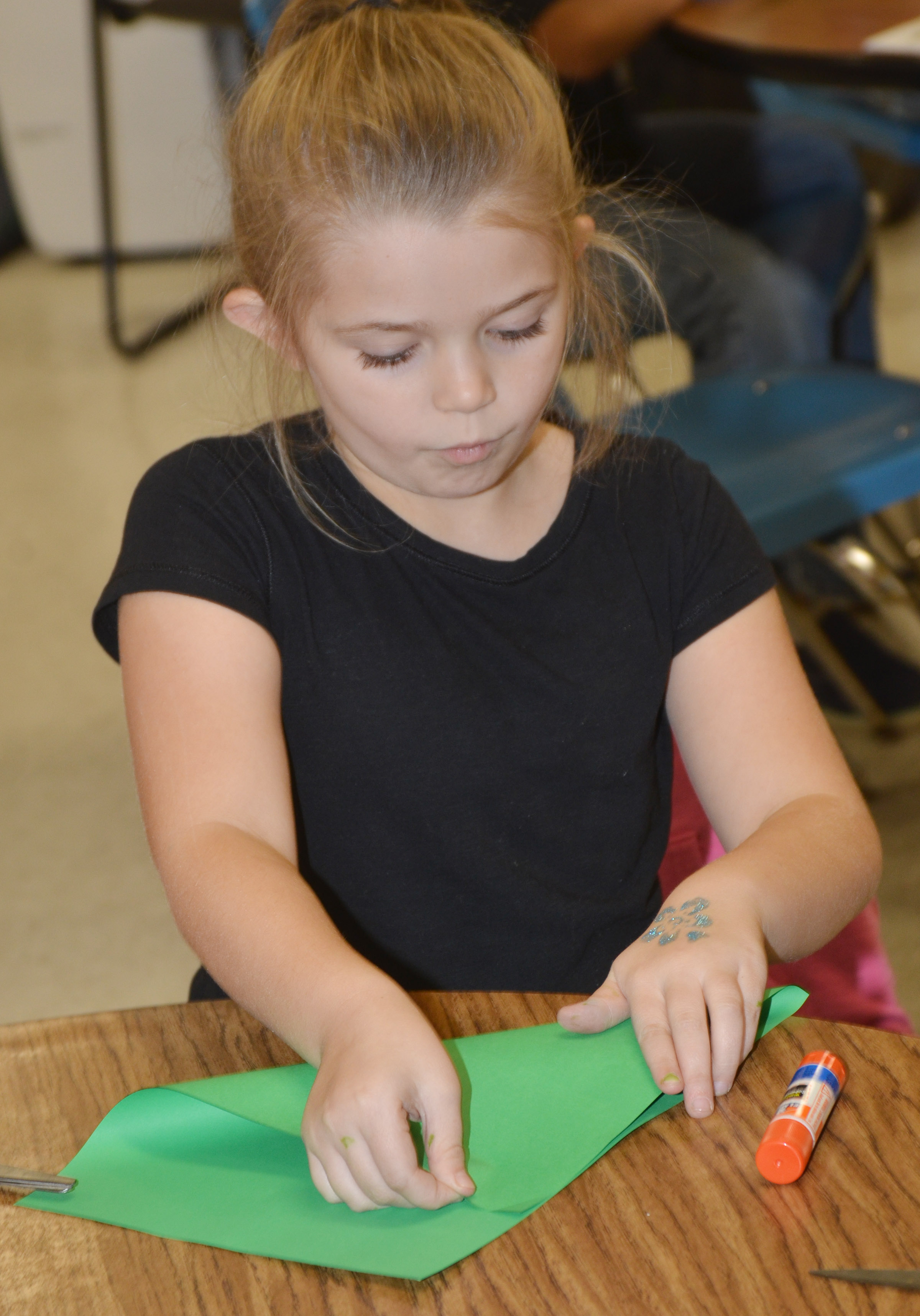 CES third-grader Chyanne Christie folds her paper to make her Christmas tree.
